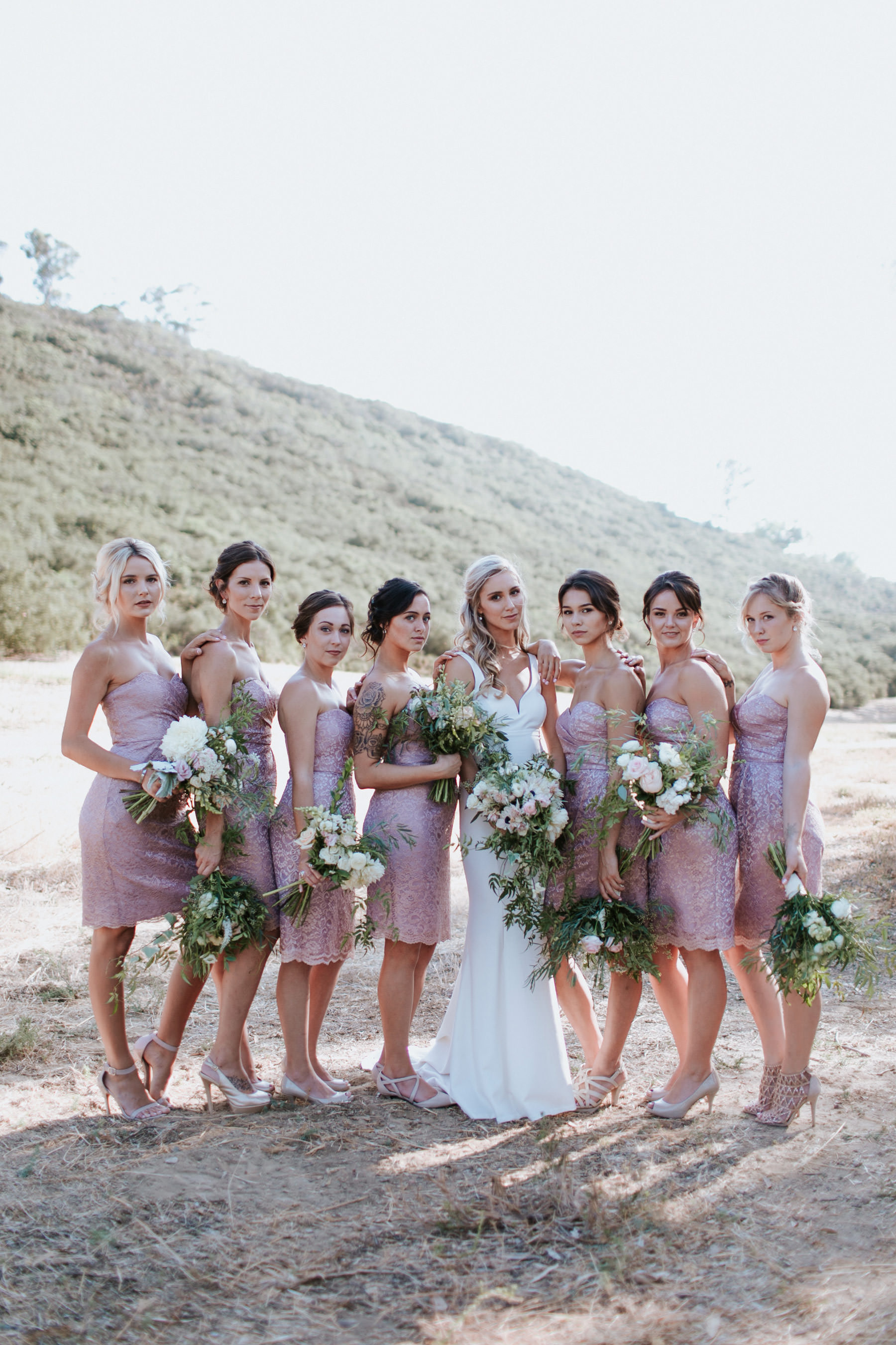 Modern bride with bridesmaids in metallic pink champagne dresses
