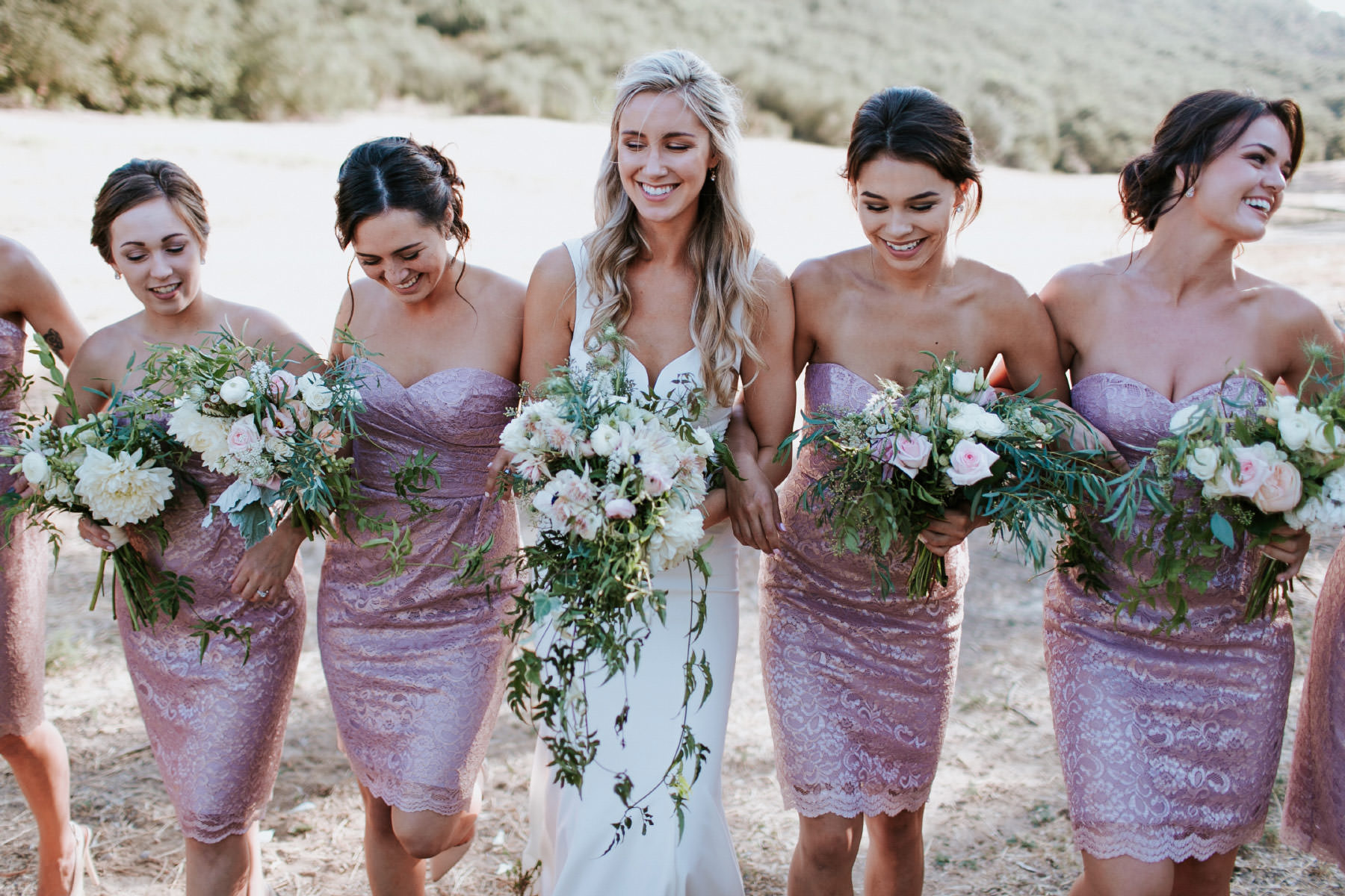 Modern bride walking with bridesmaids in metallic pink champagne dresses