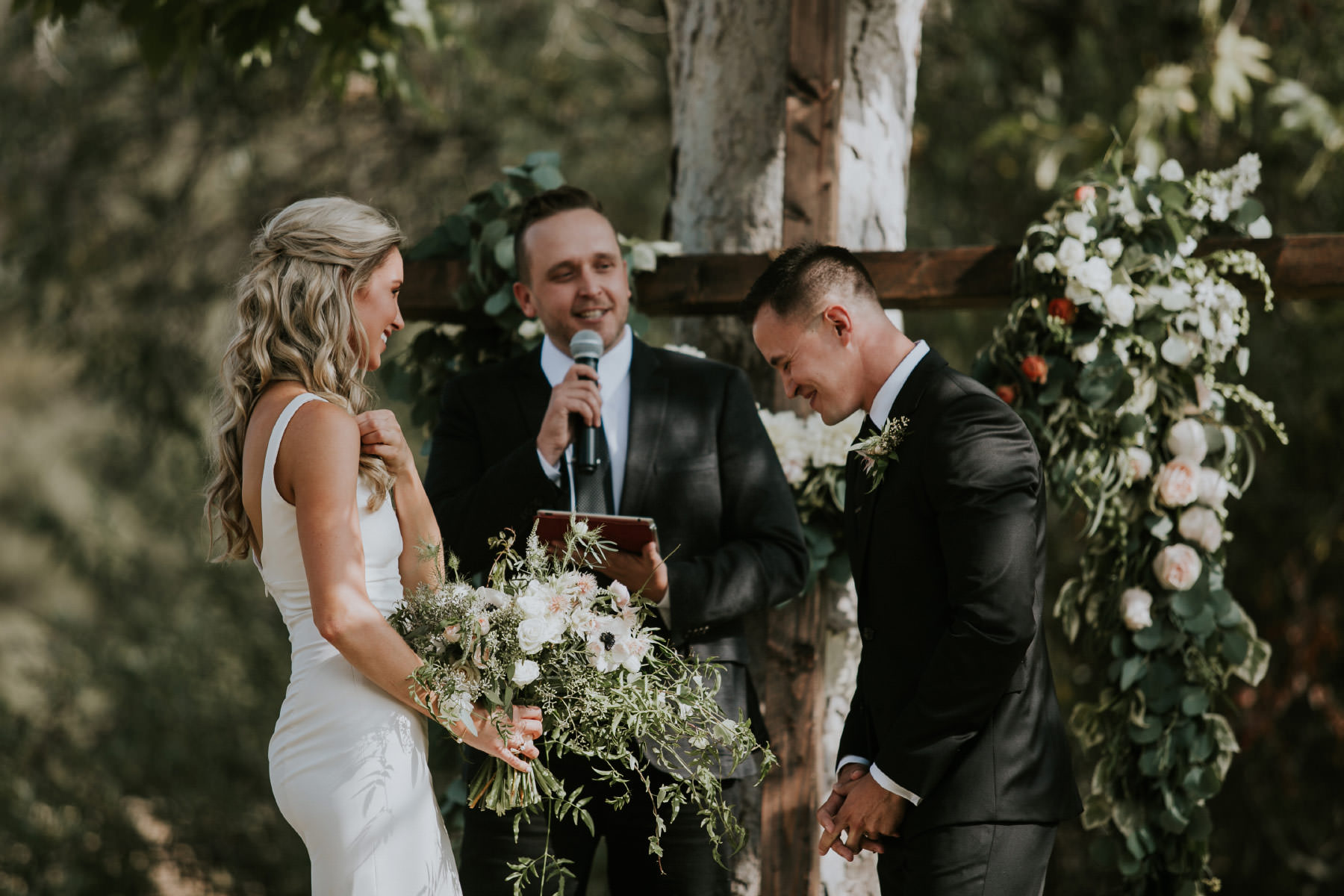 Bride and groom laughing during outdoor ceremony in San Diego