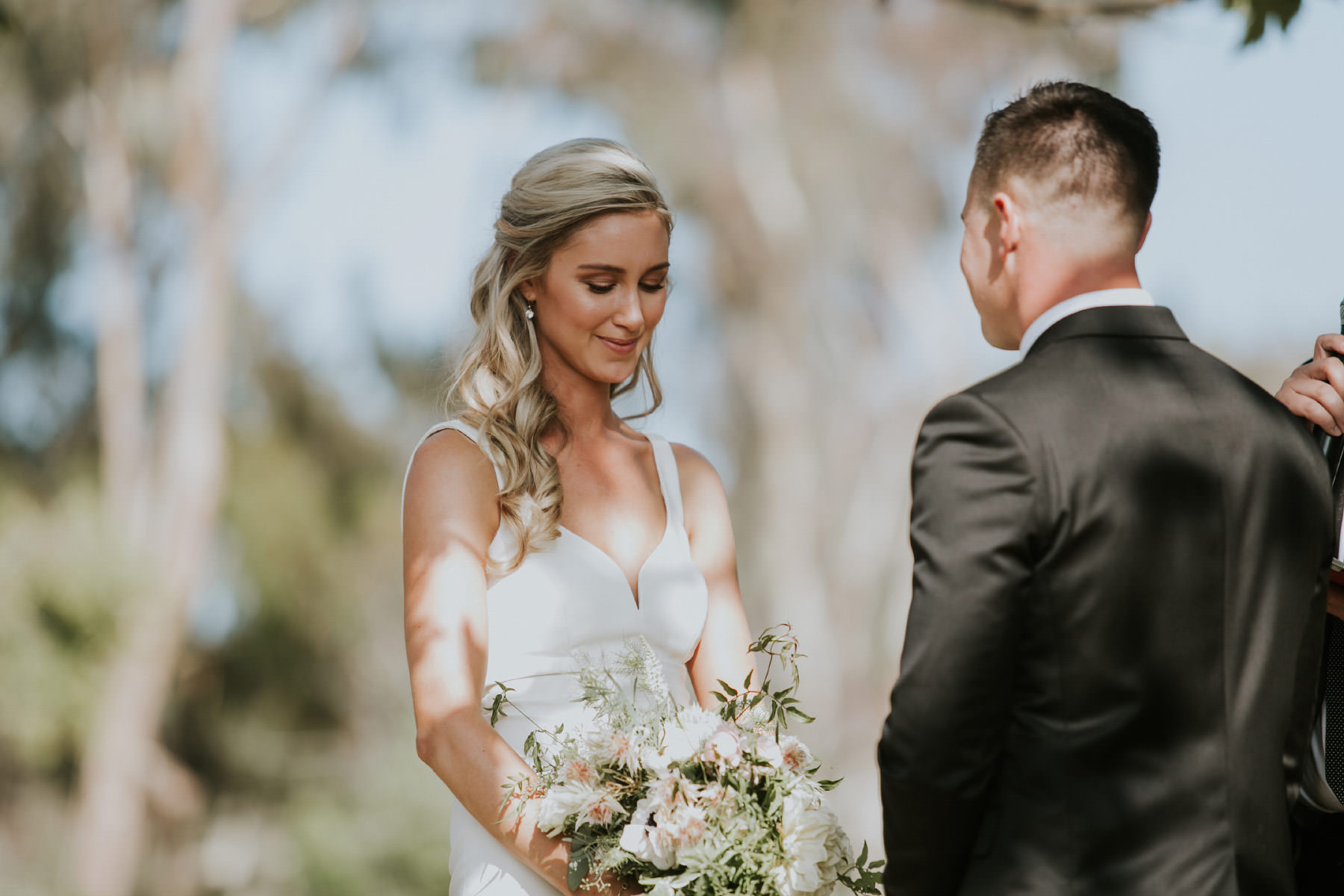 Bride blushing during outdoor ceremony in San Diego