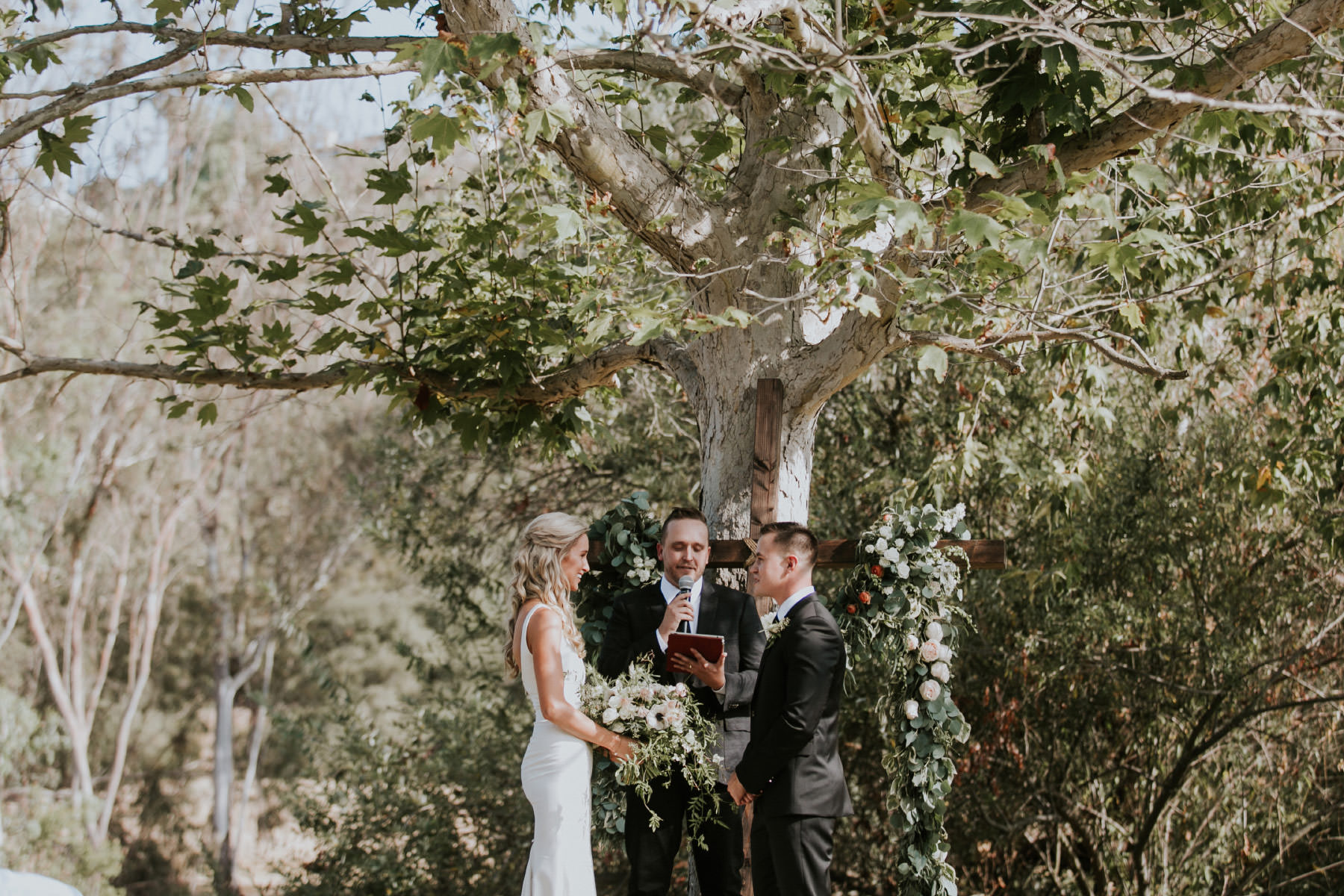 Bride and groom getting married under a tree in Rancho Santa Fe