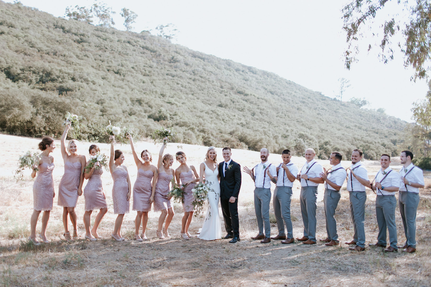 Bride and groom posed with entire bridal party being silly
