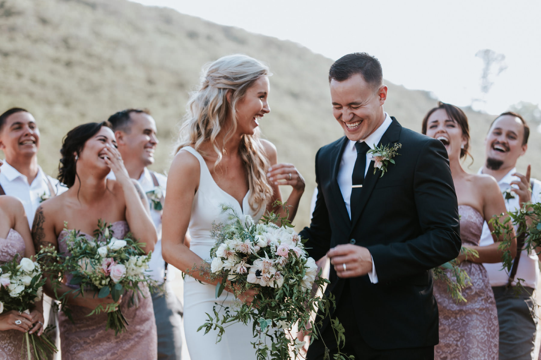 Candid of bride and groom laughing with bridal party