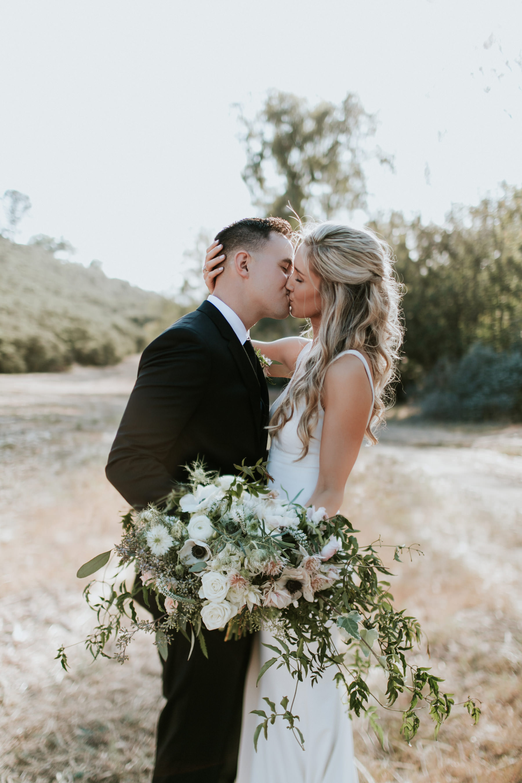 Bride and groom editorial pose with cascading bouquet