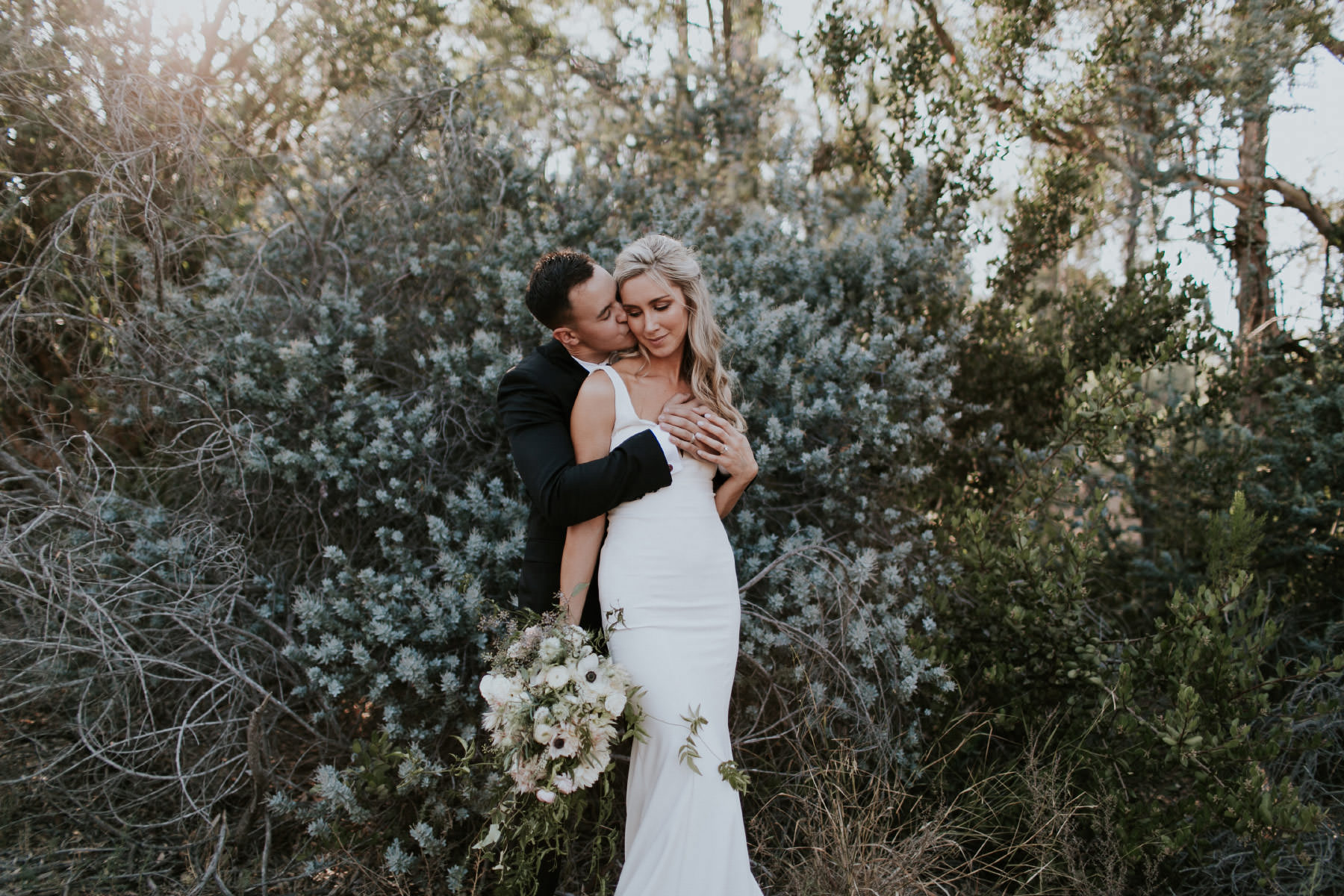 Bride and groom embracing outdoors in San Diego