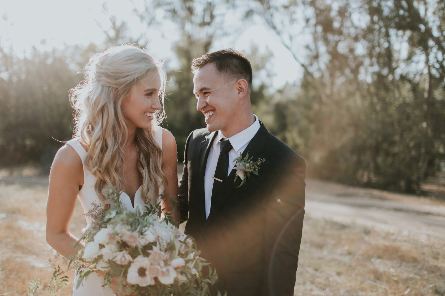 Bride and groom laughing in field during golden hour in Rancho Santa Fe