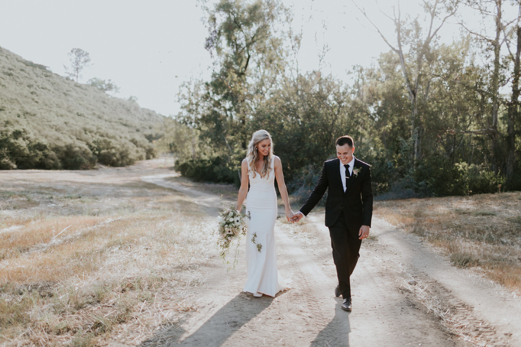 Bride and groom walking holding hands in field at Rancho Santa Fe estate