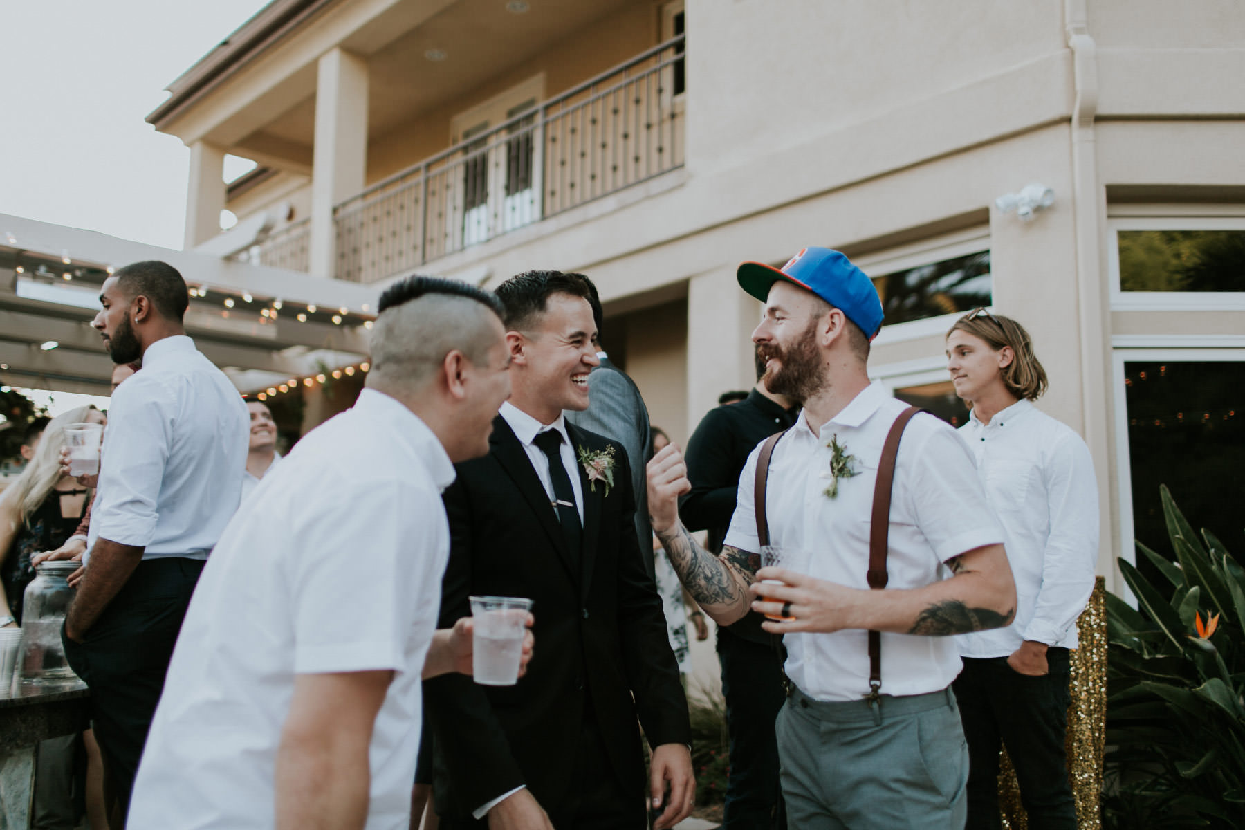 Candid groom mingling with guests at cocktail hour
