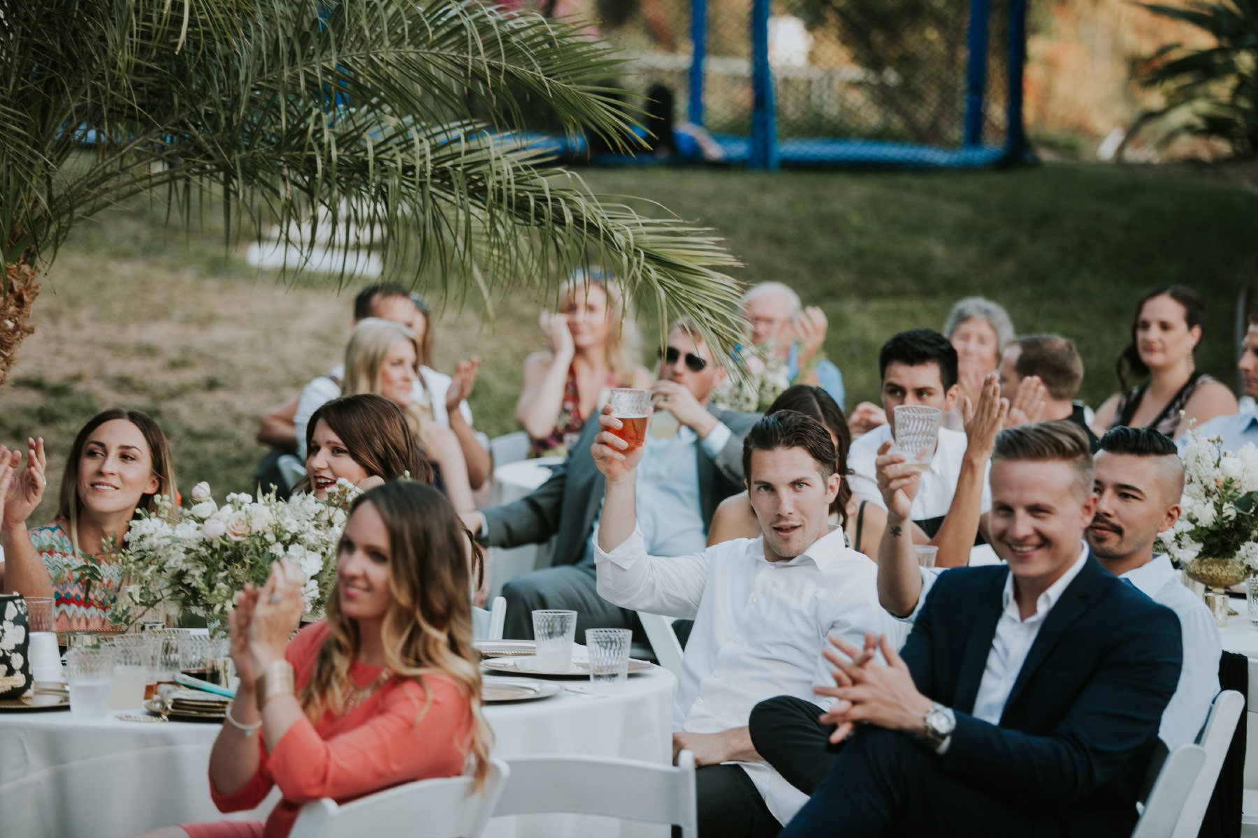 Guests clapping during wedding speeches at San Diego backyard wedding