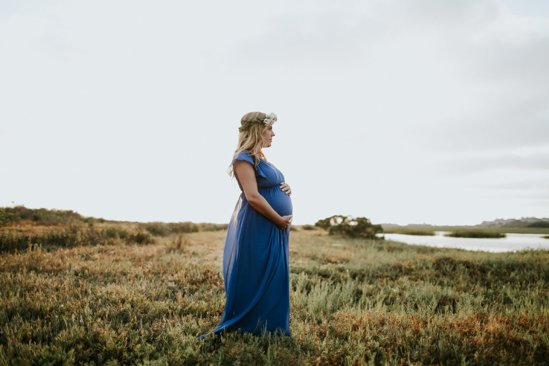 Maternity goddess wearing a blue dress and flower crown during golden hour at San Elijo Lagoon in San Diego