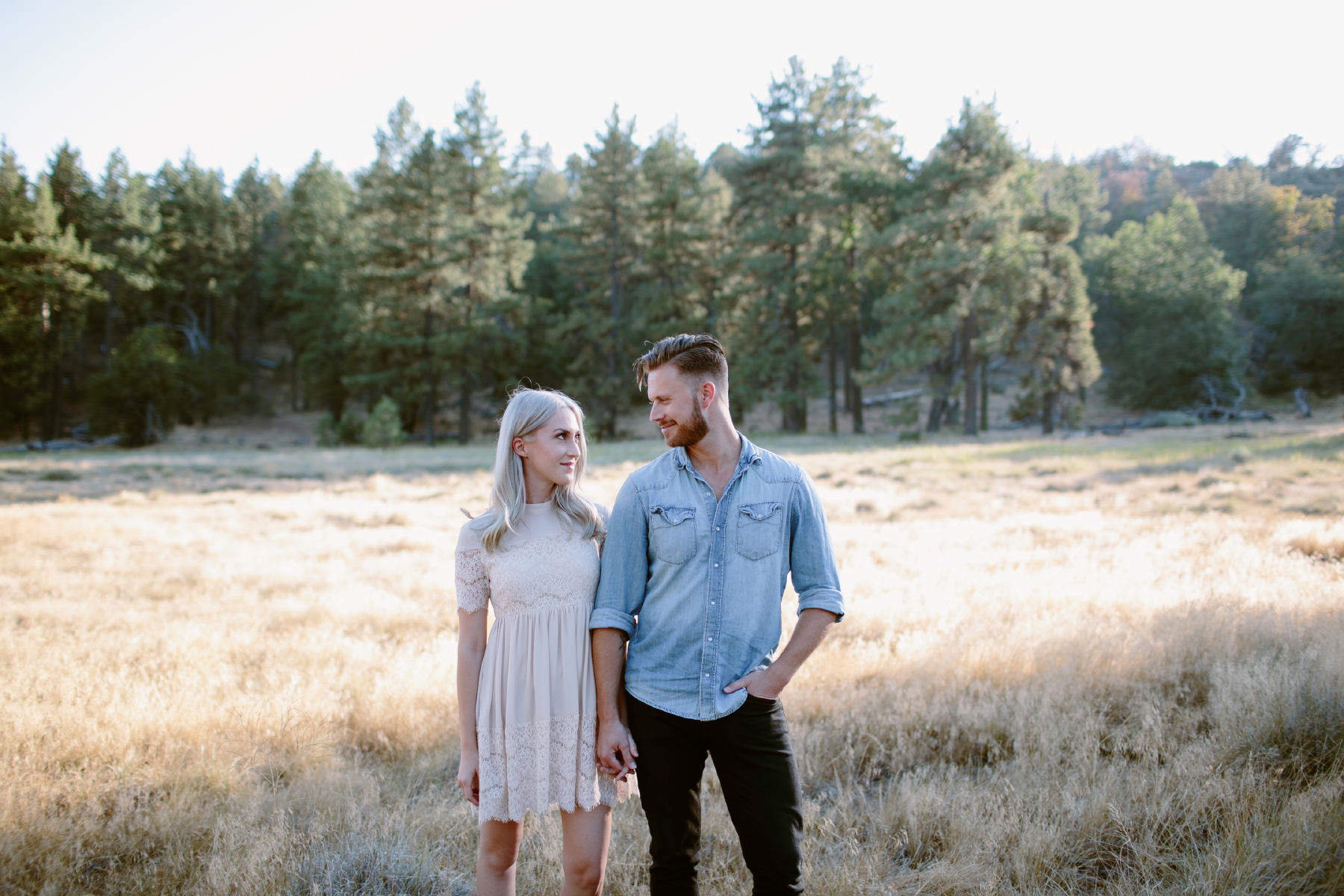 Hip couple standing in a forest meadow in San Diego