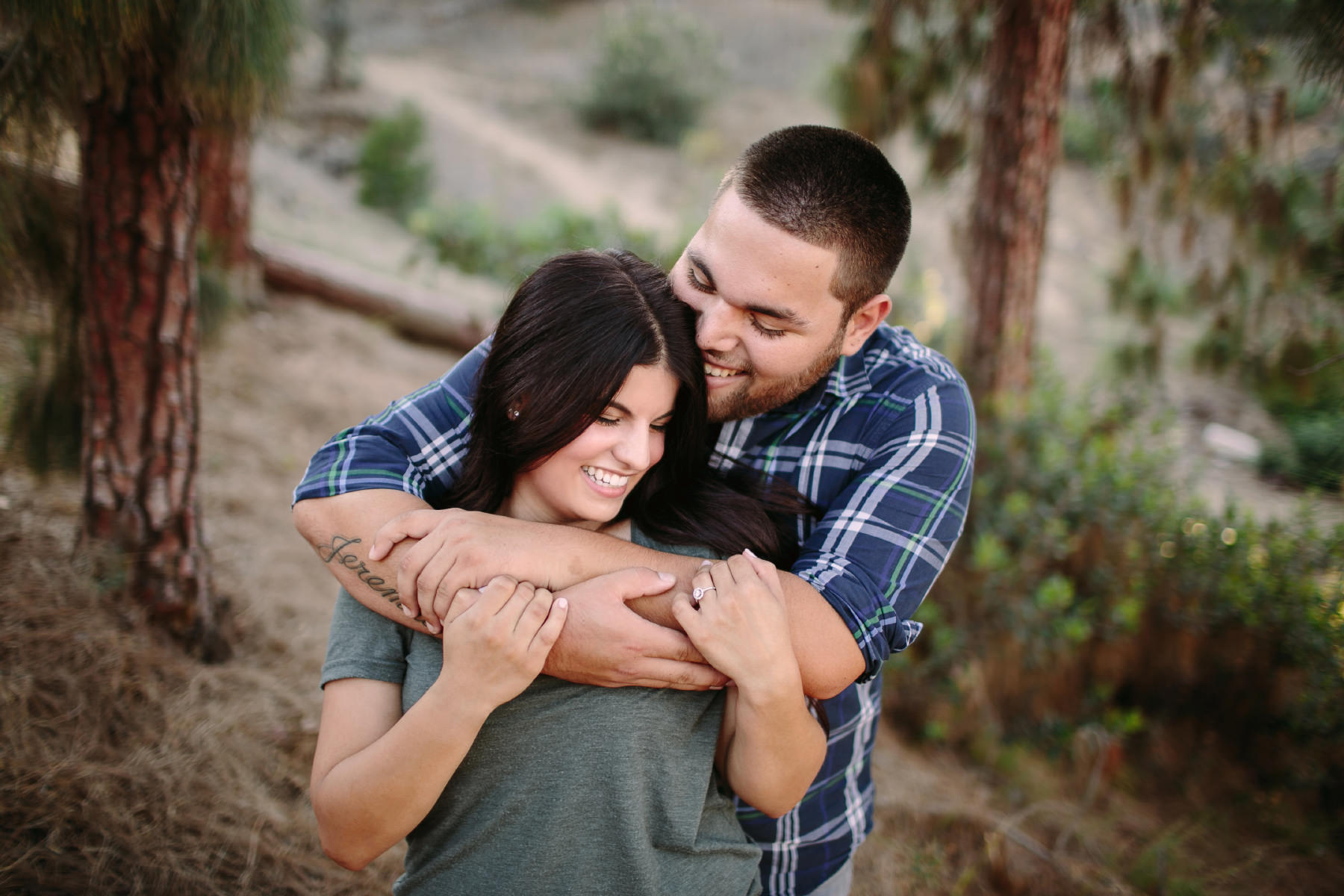 Engaged couple embracing in the redwood trees of Bridle Trail