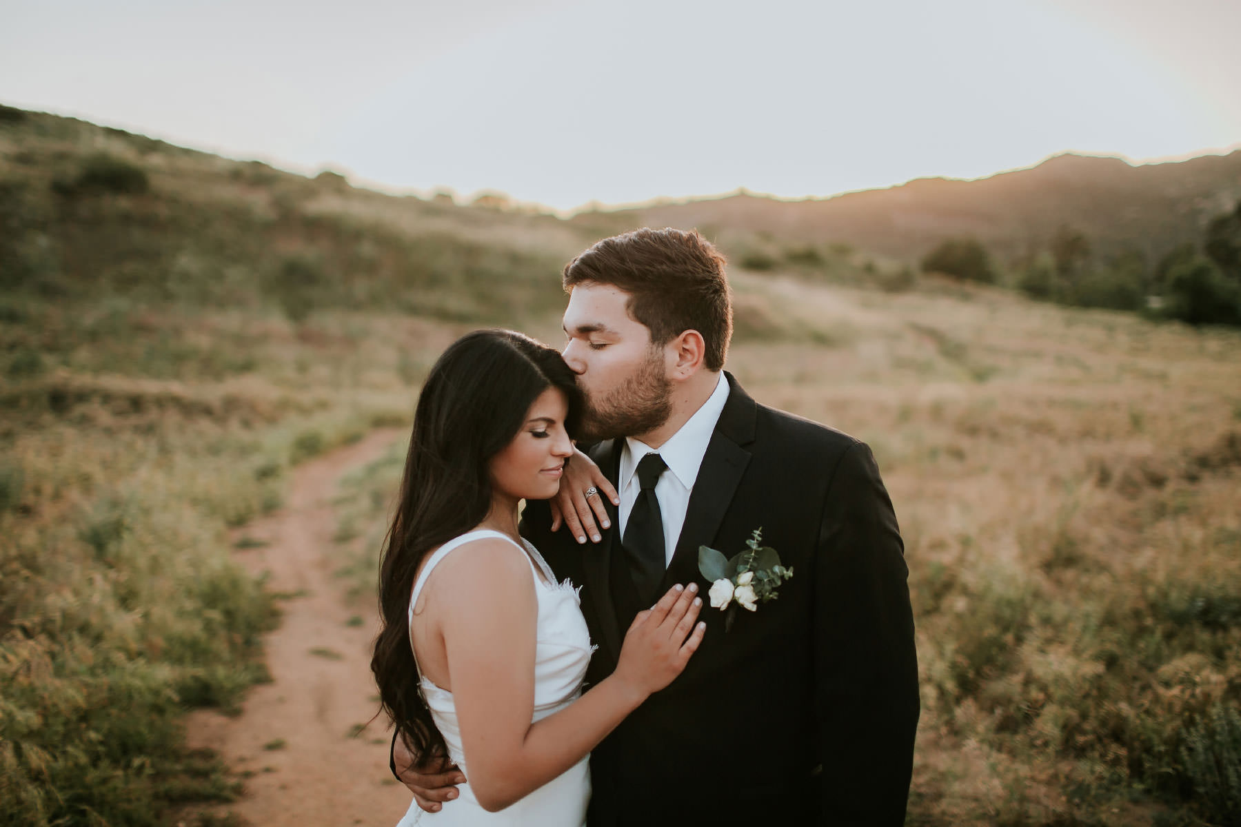 Bride and groom romantics in an open field at golden hour in San Diego
