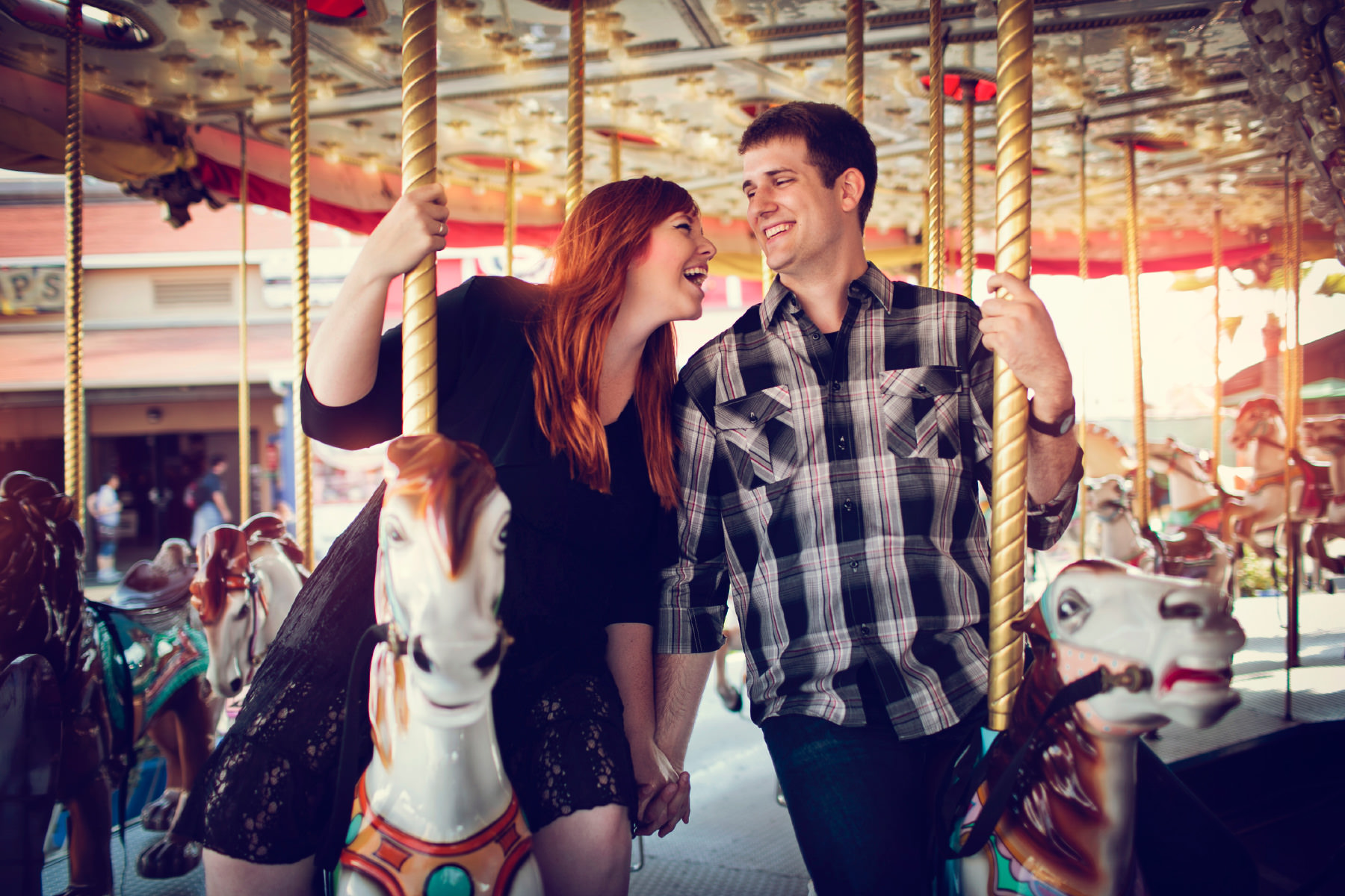 Cute engaged couple riding on a carousel at the San Diego County Fair