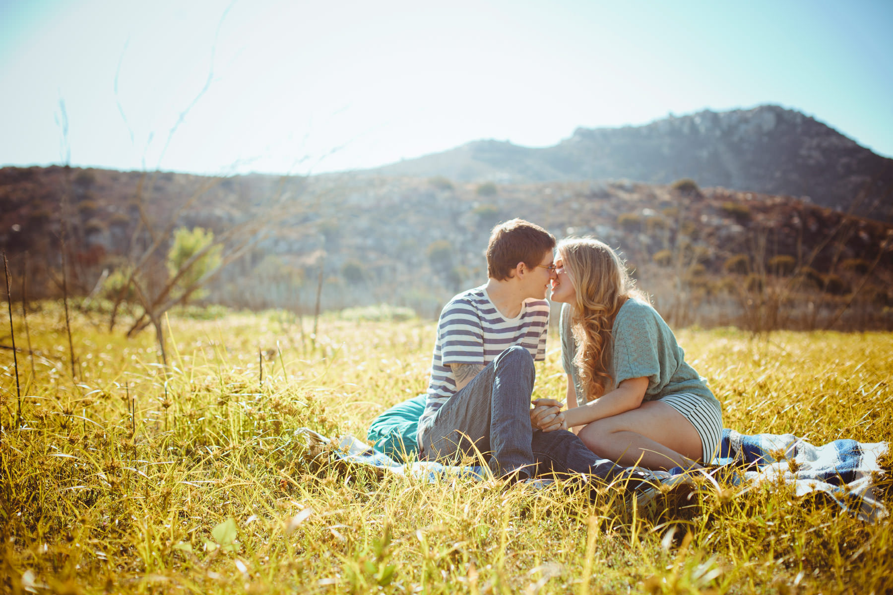 Kissing on a picnic blanket at Lake Hodges