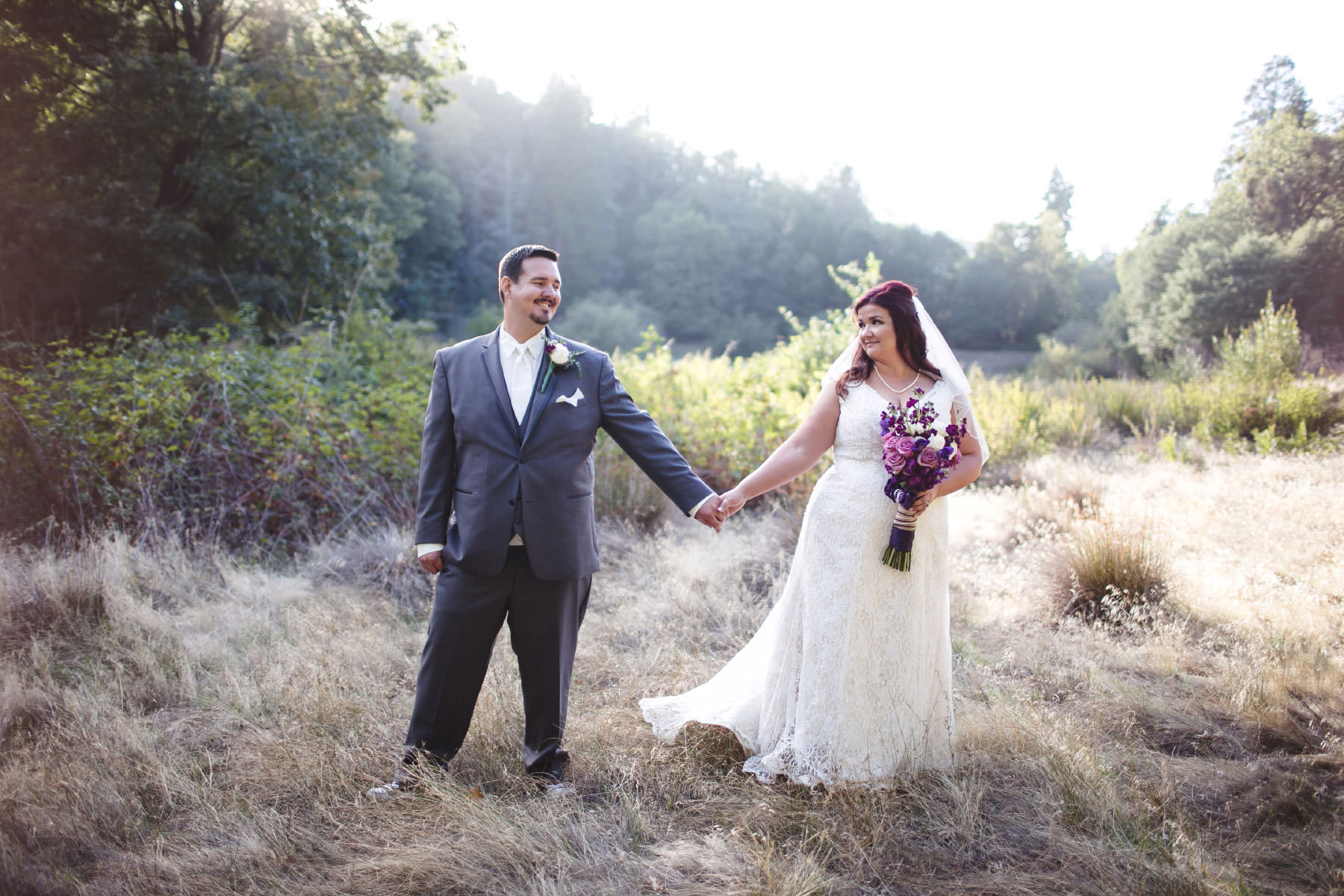 Bride and groom posing in a field at Baileys Palomar Resort