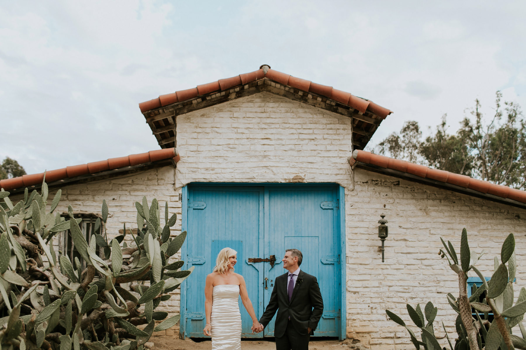 Bride and groom holding hands in front of a blue door at Leo Carrillo Ranch