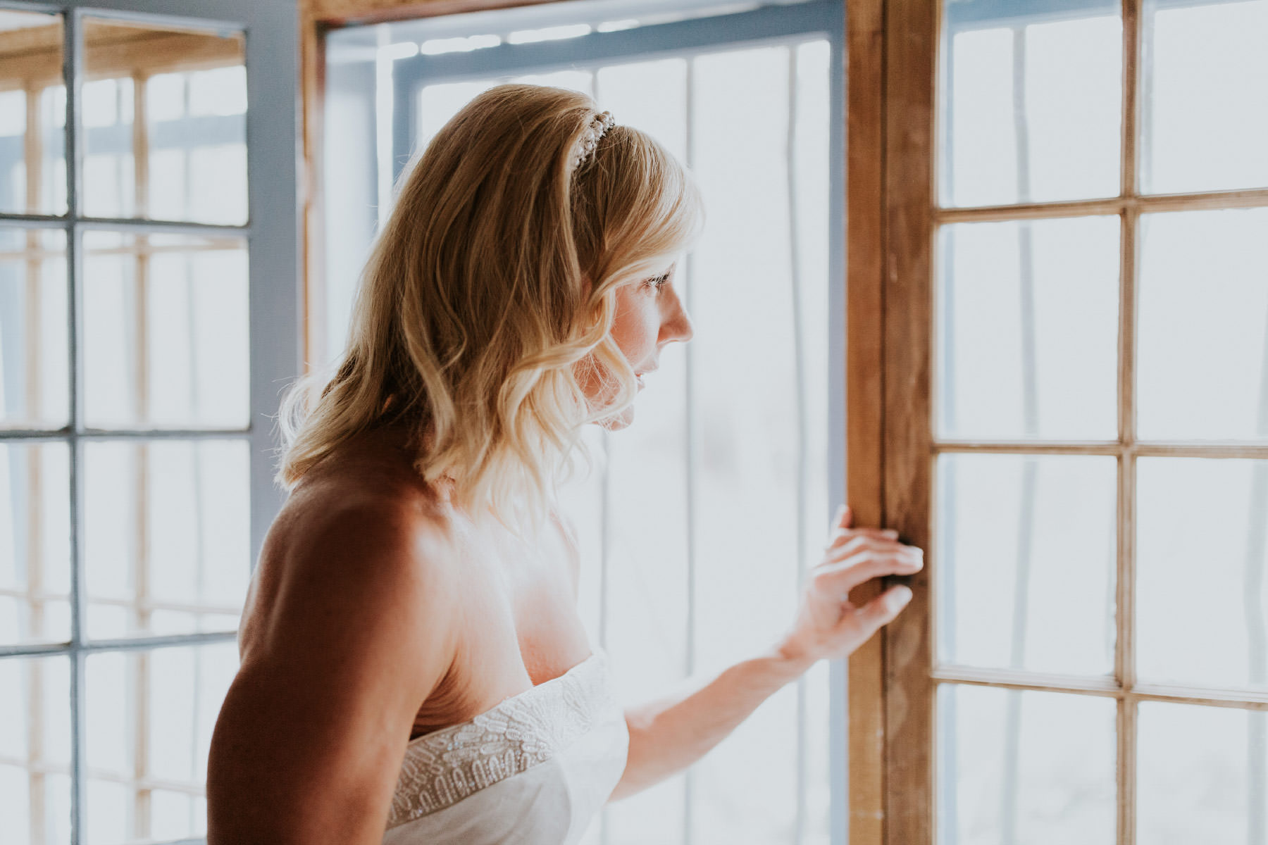 Bride staring out window at Leo Carrillo Ranch