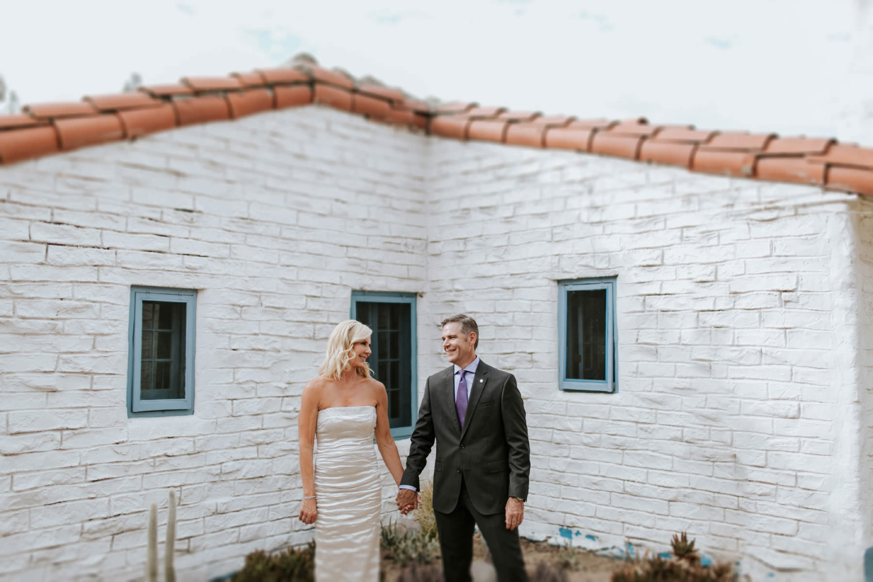 Bride and groom posing outside hacienda at Leo Carrillo Ranch