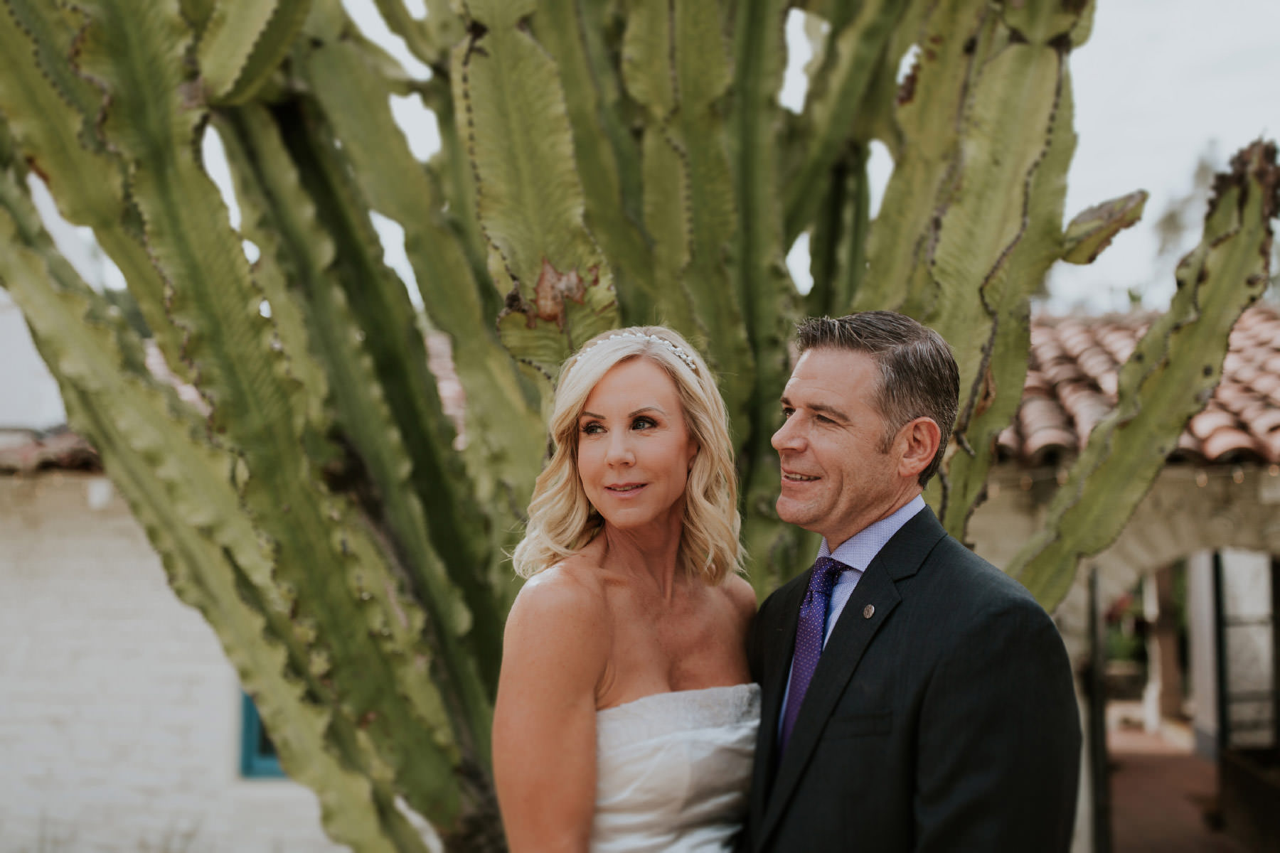 Bride and groom posing in front of cactus at Leo Carrillo Ranch