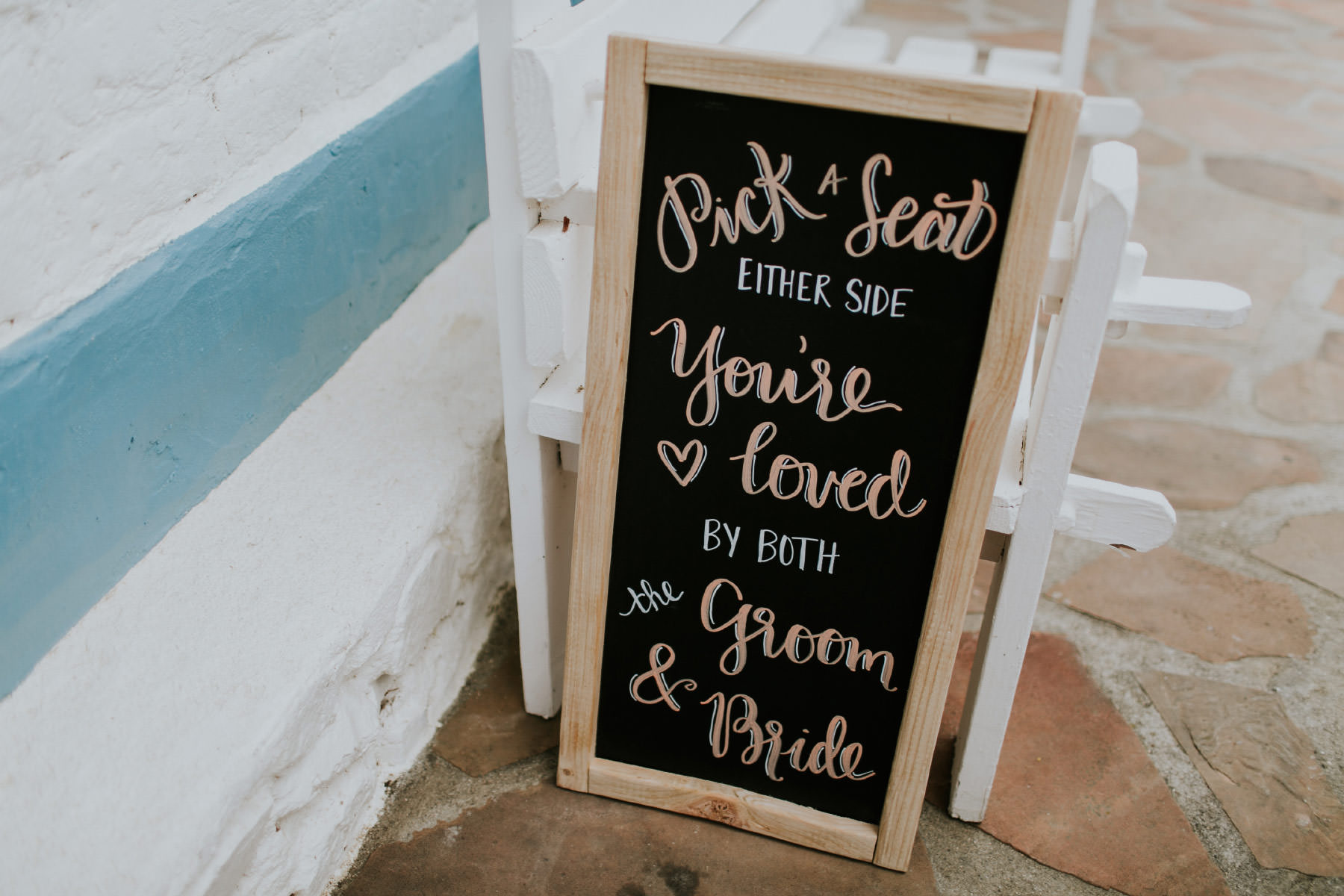 Pick a seat either side you're loved by both the groom and bride sign
