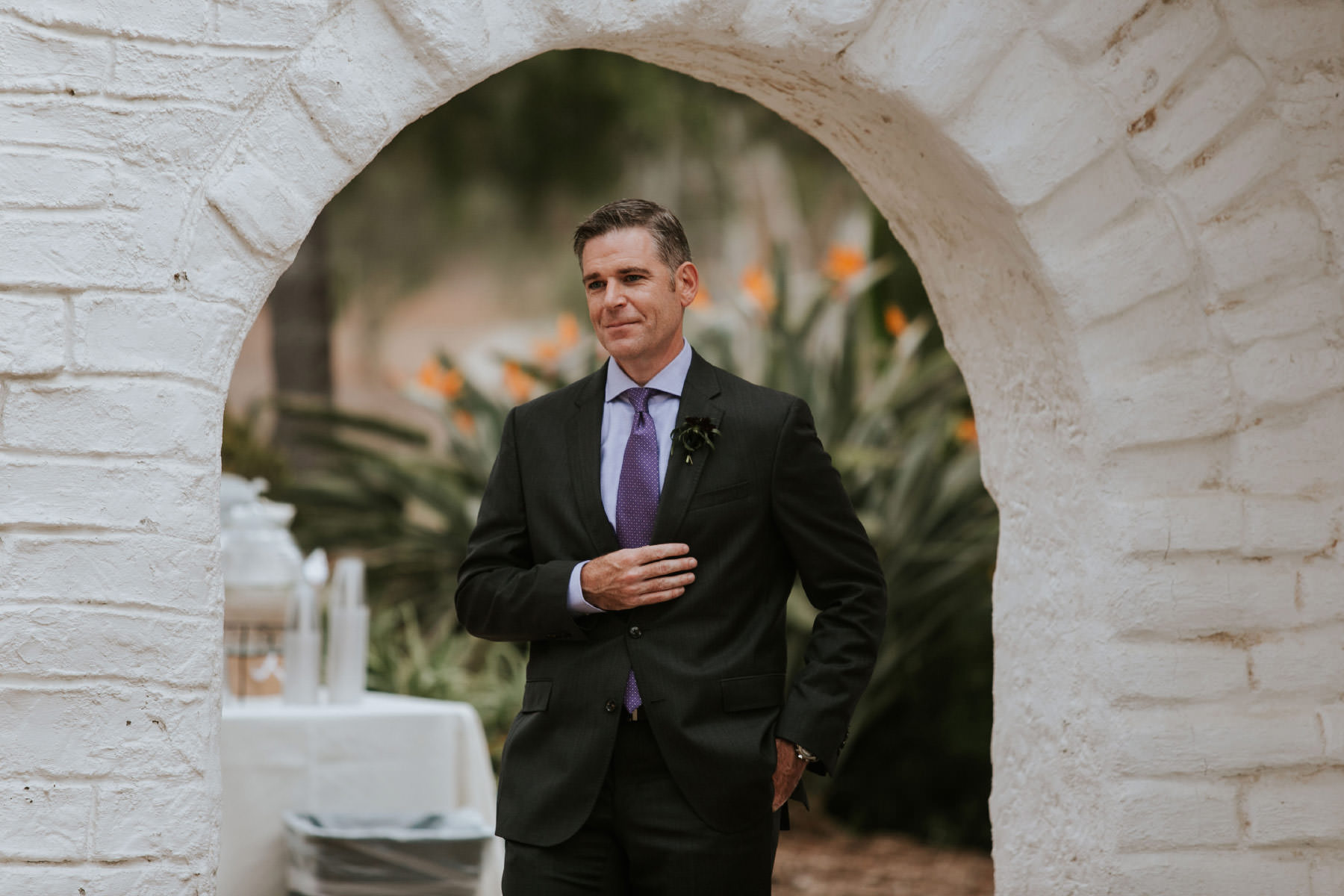 Groom walking through archway at Leo Carrillo Ranch wedding