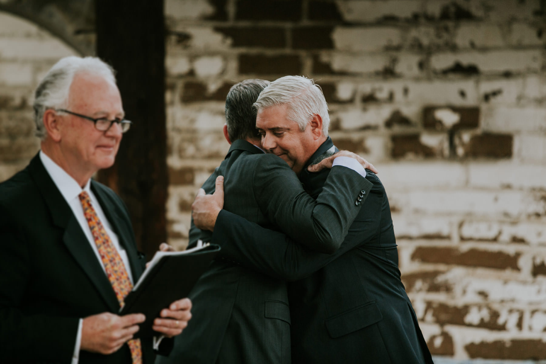 Groom and best man hugging during ceremony