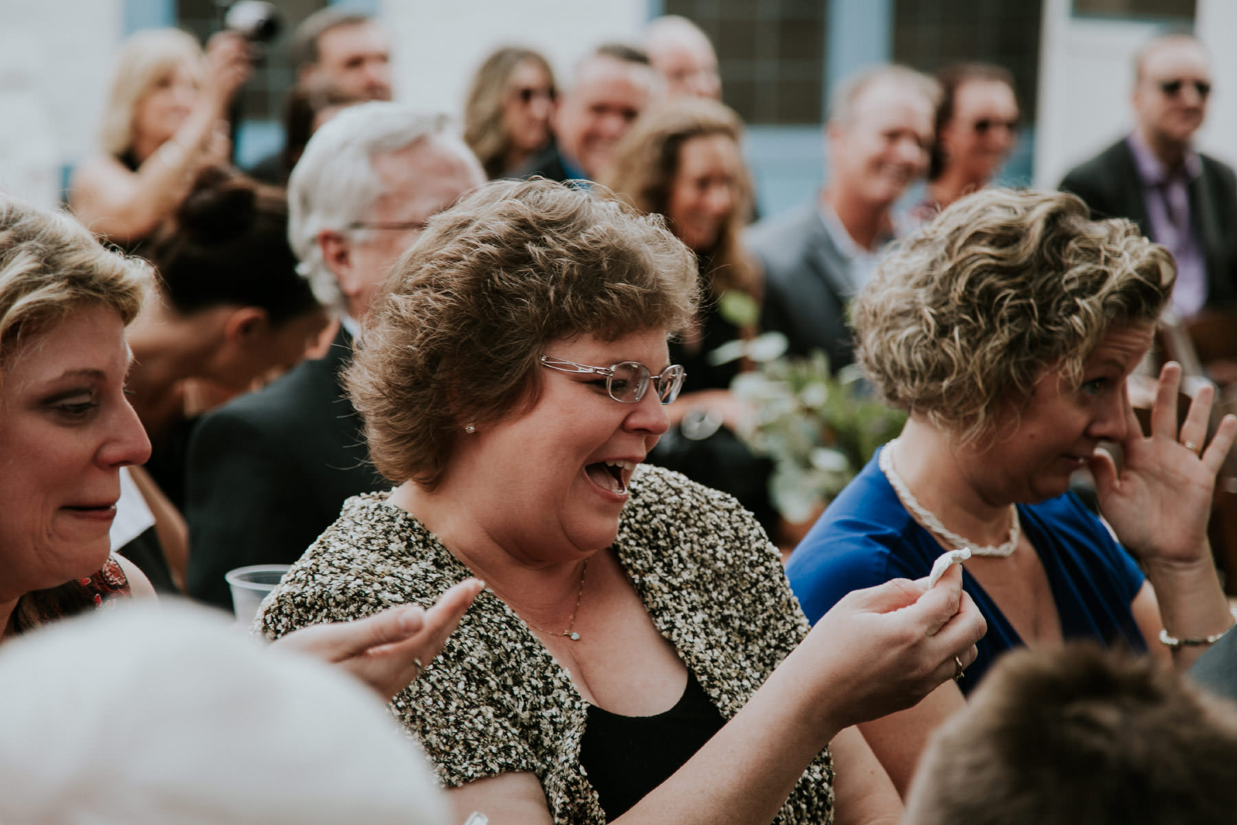 Guests wiping away tears while laughing during ceremony