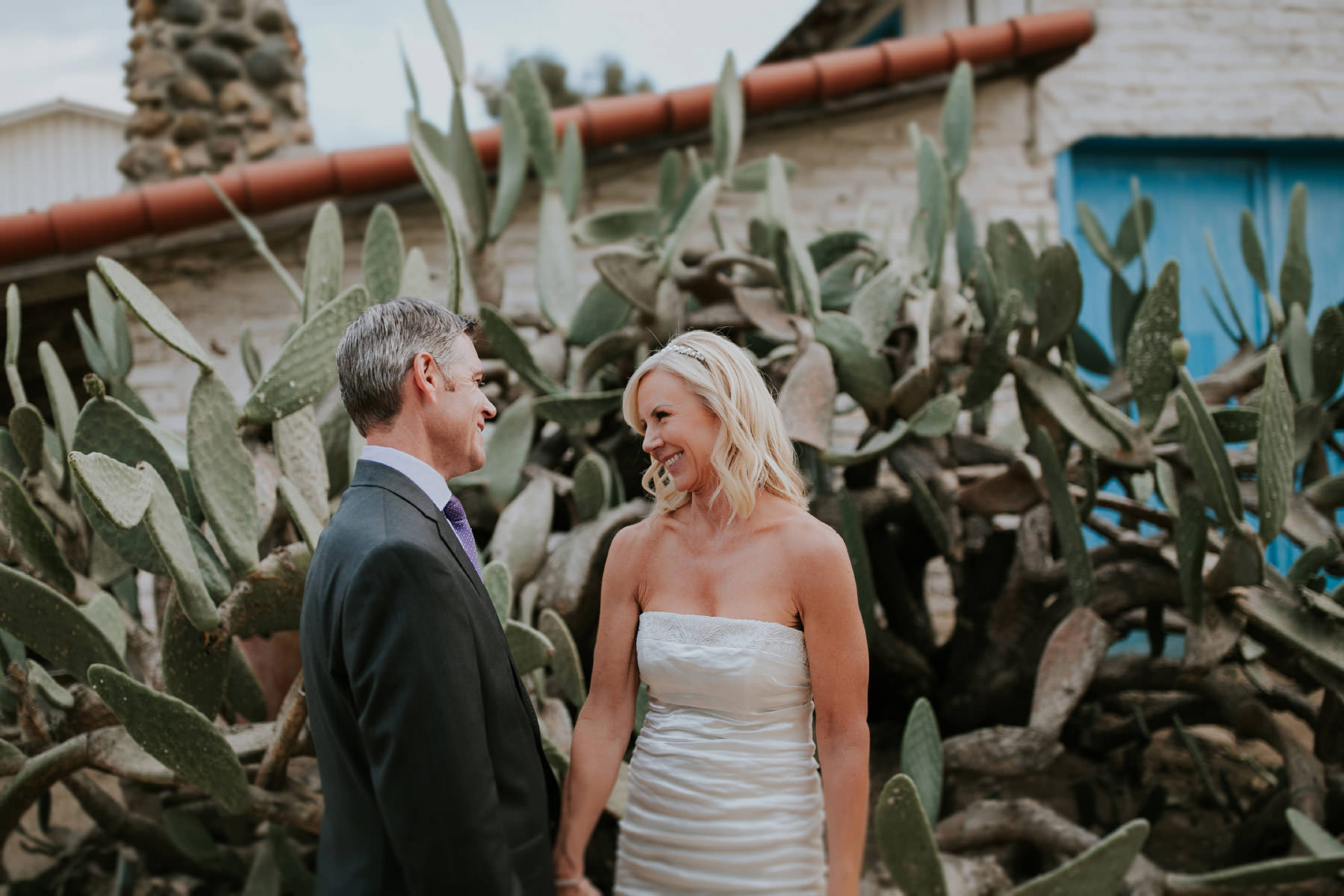Bride and groom laughing in front of cactus at Leo Carrillo Ranch