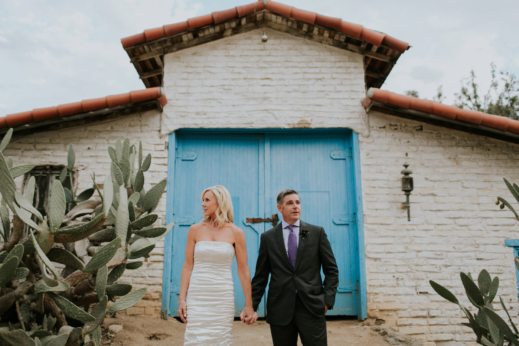 Bride and groom pose in front of blue door at Leo Carrillo Ranch