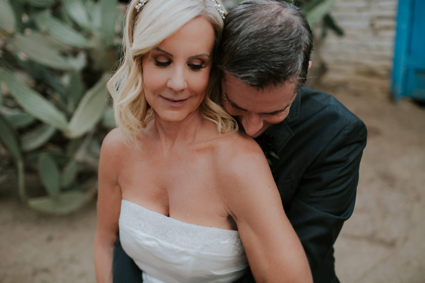 Groom kissing bride on shoulder at Leo Carrillo Ranch