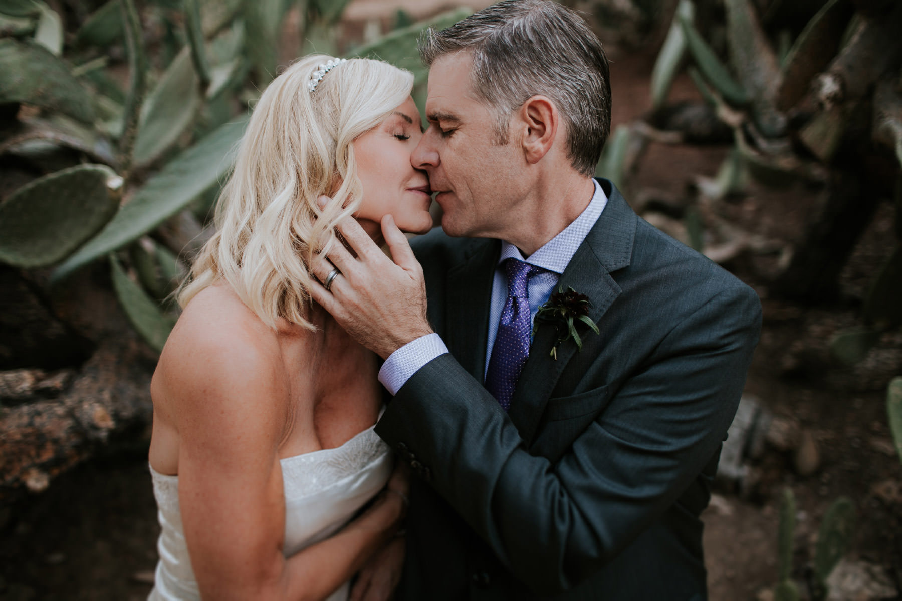 Bride and groom kissing in front of cactus at Leo Carrillo Ranch