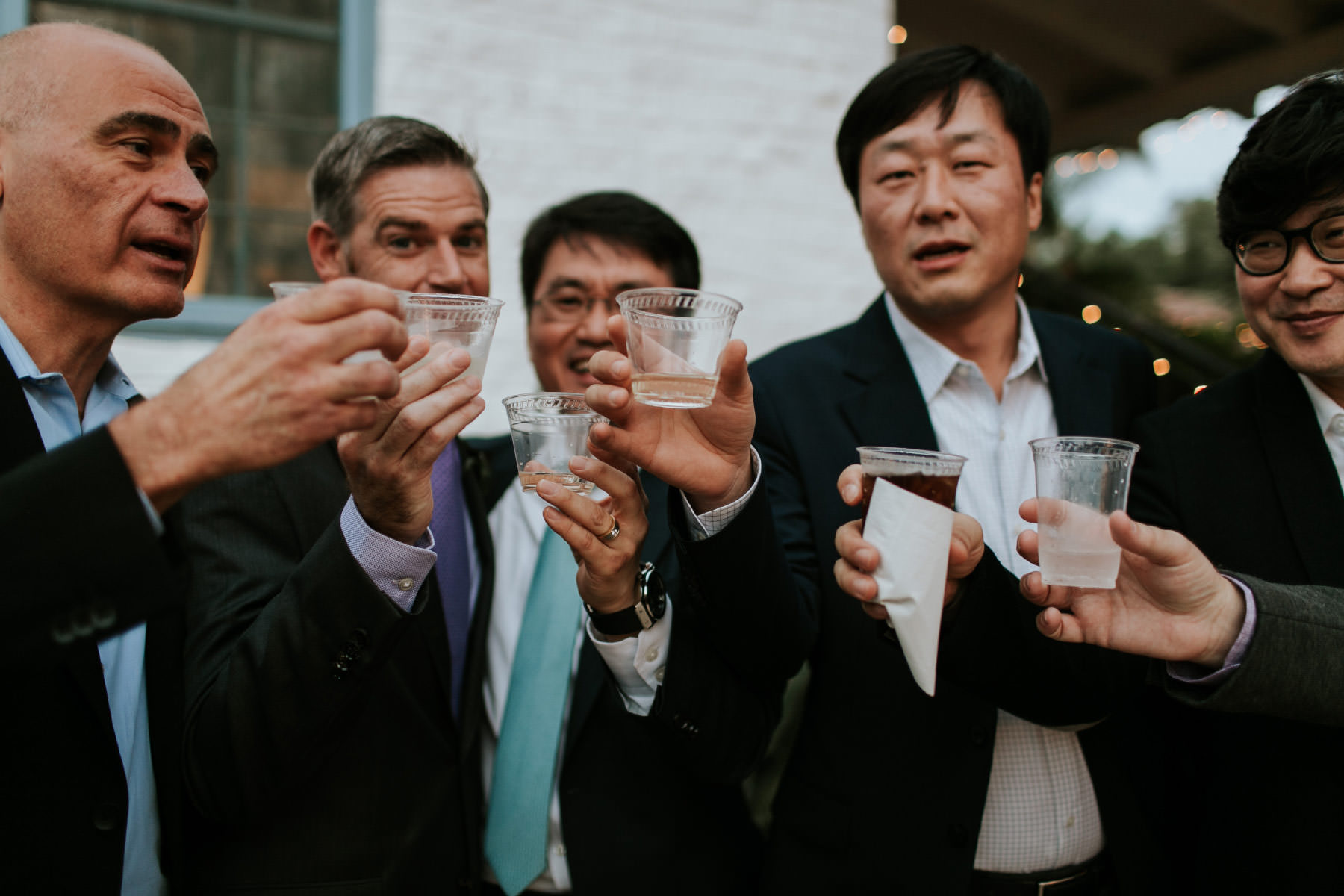 Groom and wedding guests cheersing with shots