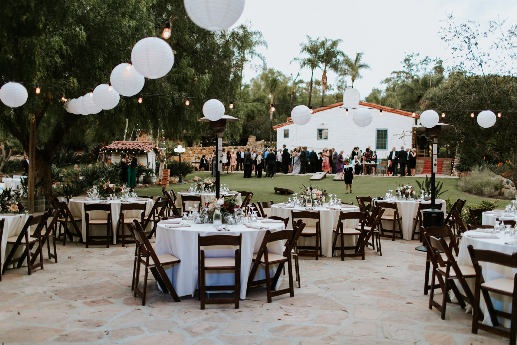 Reception table setup with string lights and paper lanterns at Leo Carrillo Ranch wedding