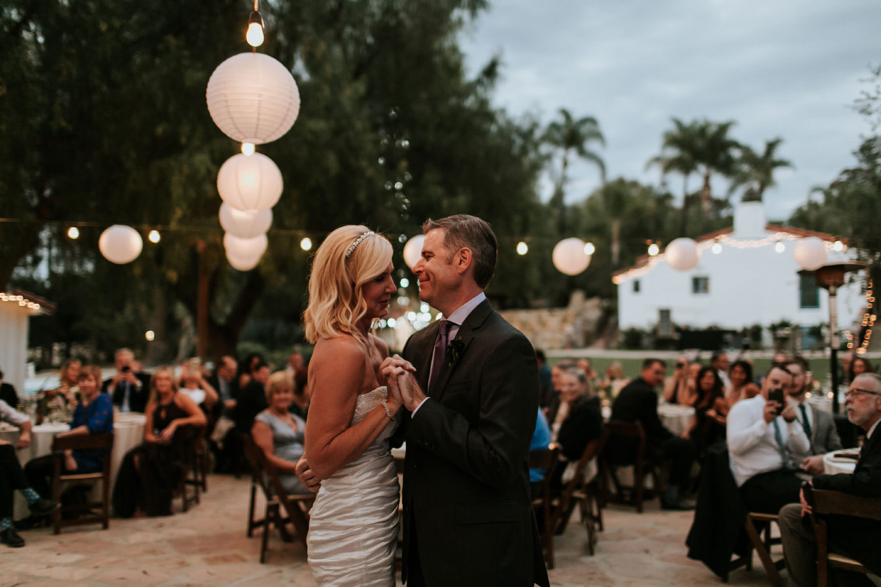 Bride and groom first dance with twinkle lights and paper lanterns