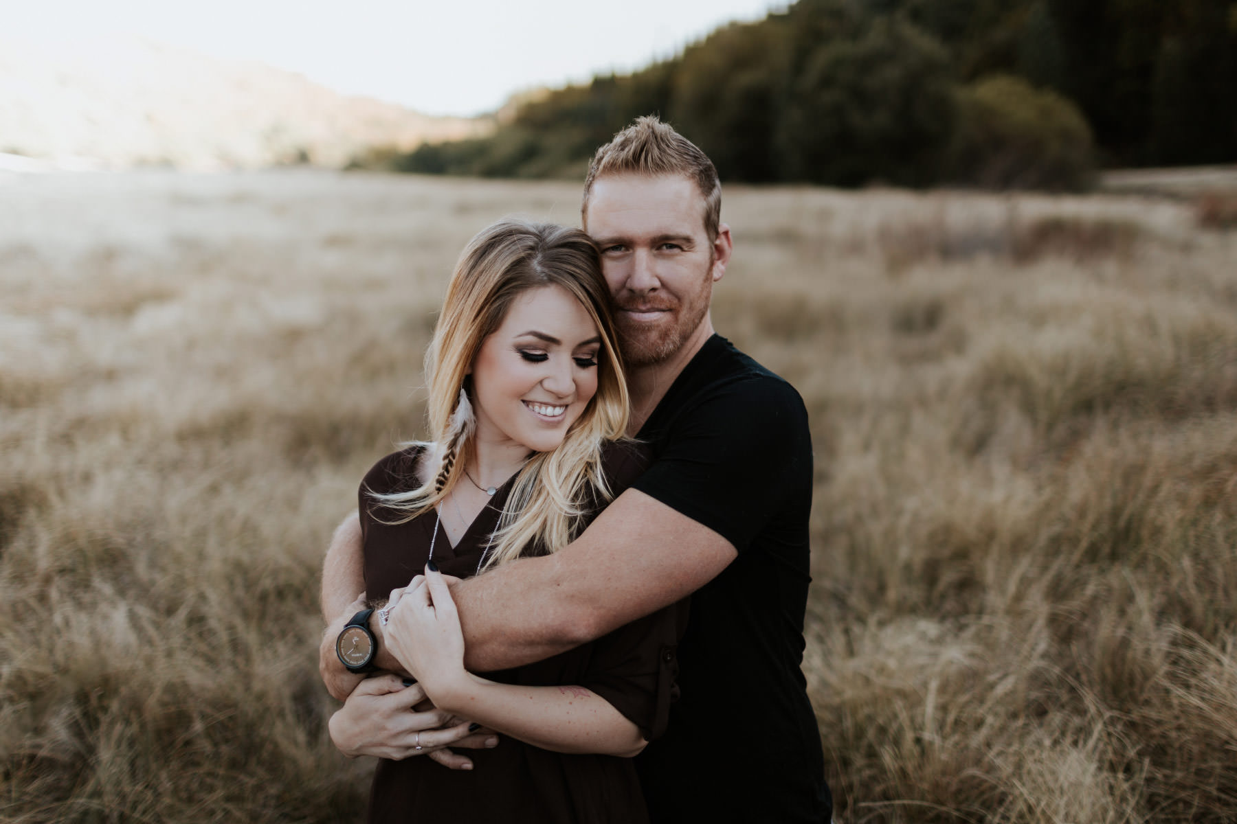 Engaged couple embracing in a field at Palomar Mountain