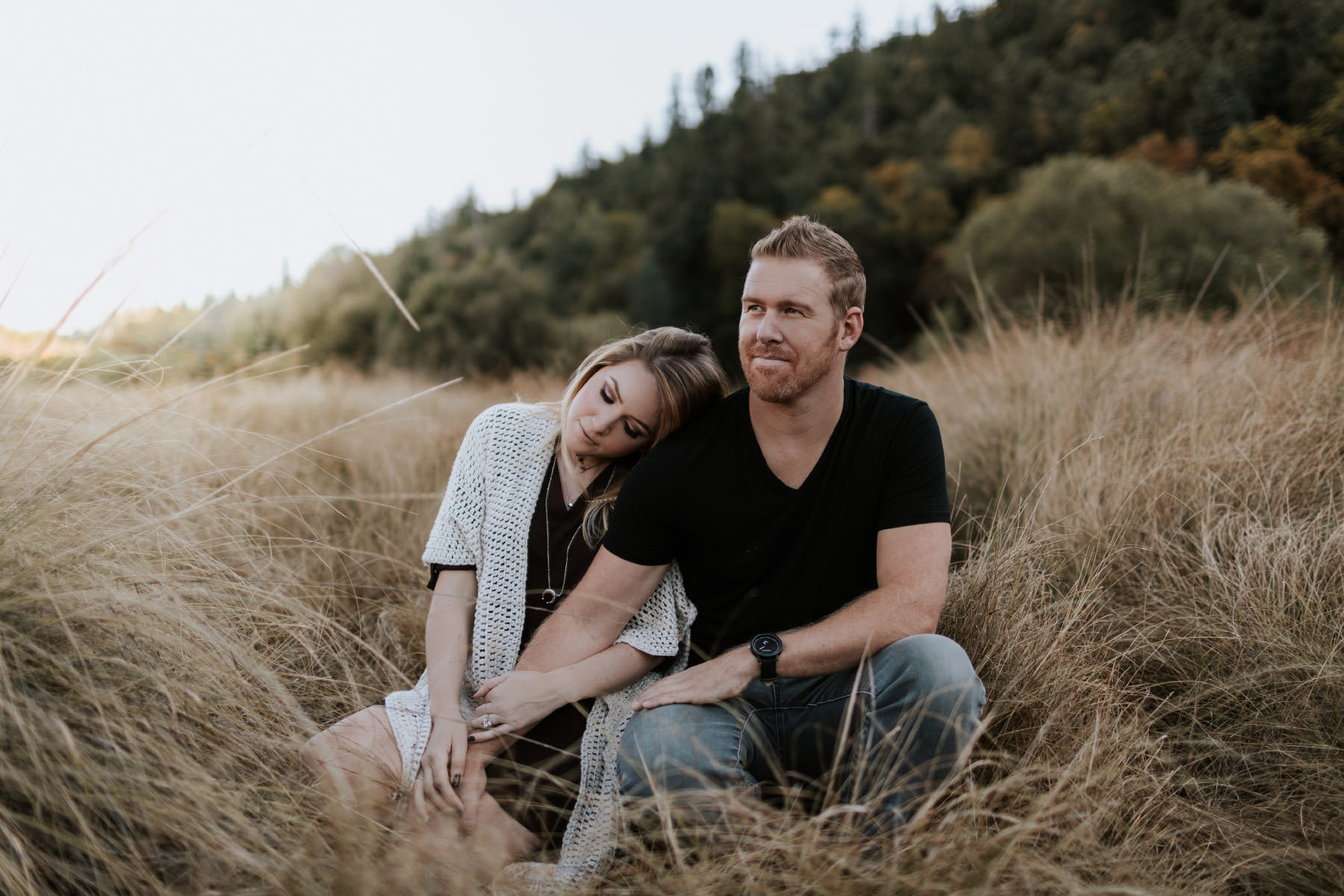 Engaged couple cuddling in a field at Palomar Mountain