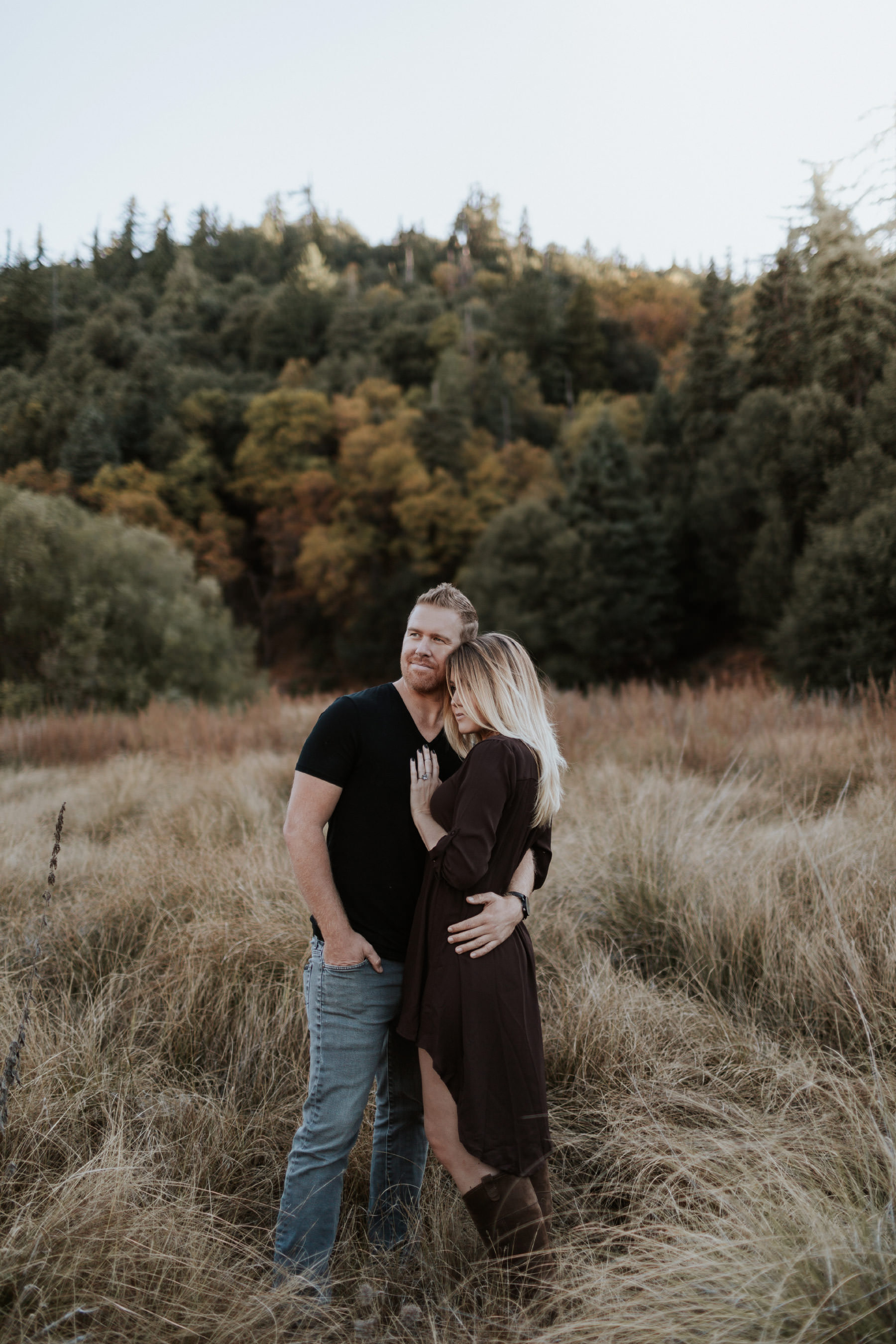 Couple embracing at Palomar Mountain with fall colored trees in the background
