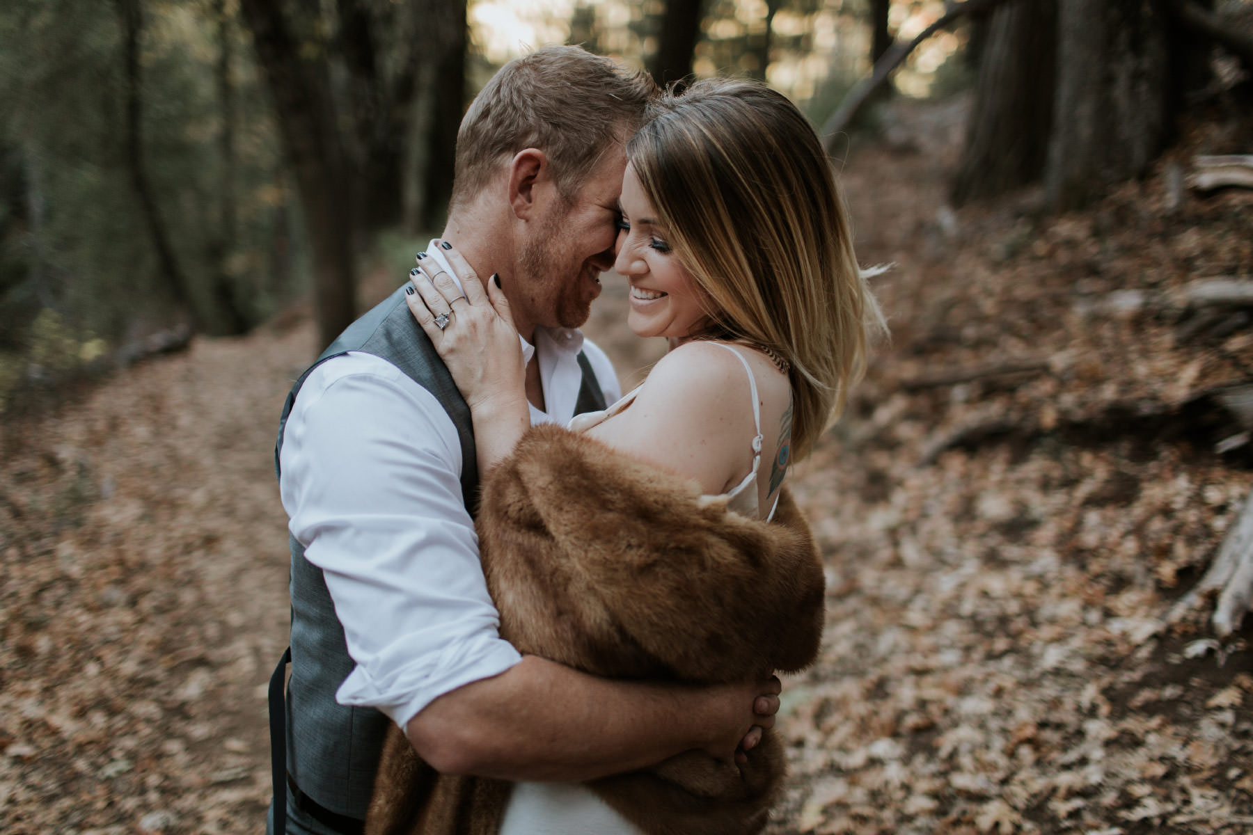 Couple laughing in forest at Palomar Mountain wearing vintage fur stole