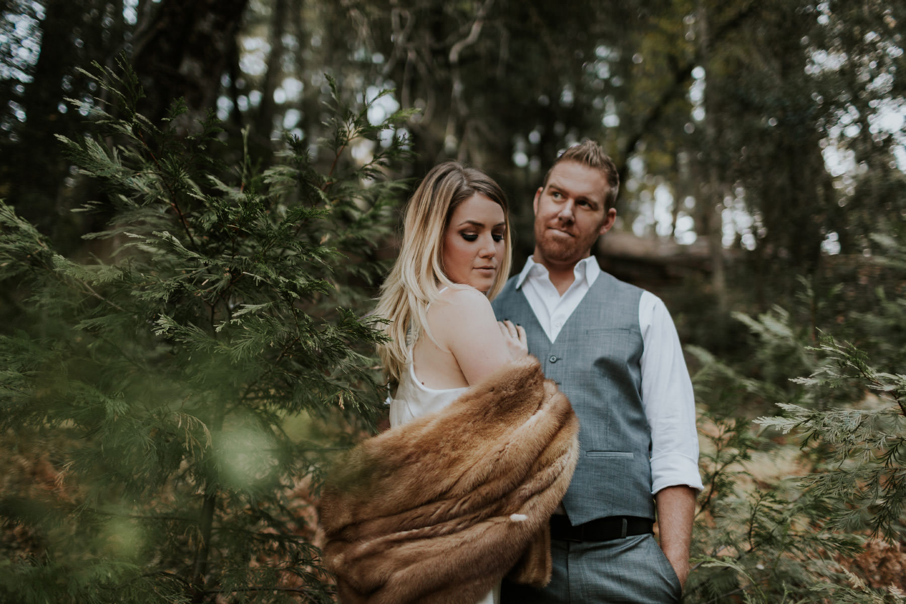 Couple posing in forest wearing vintage fur stole at Palomar Mountain