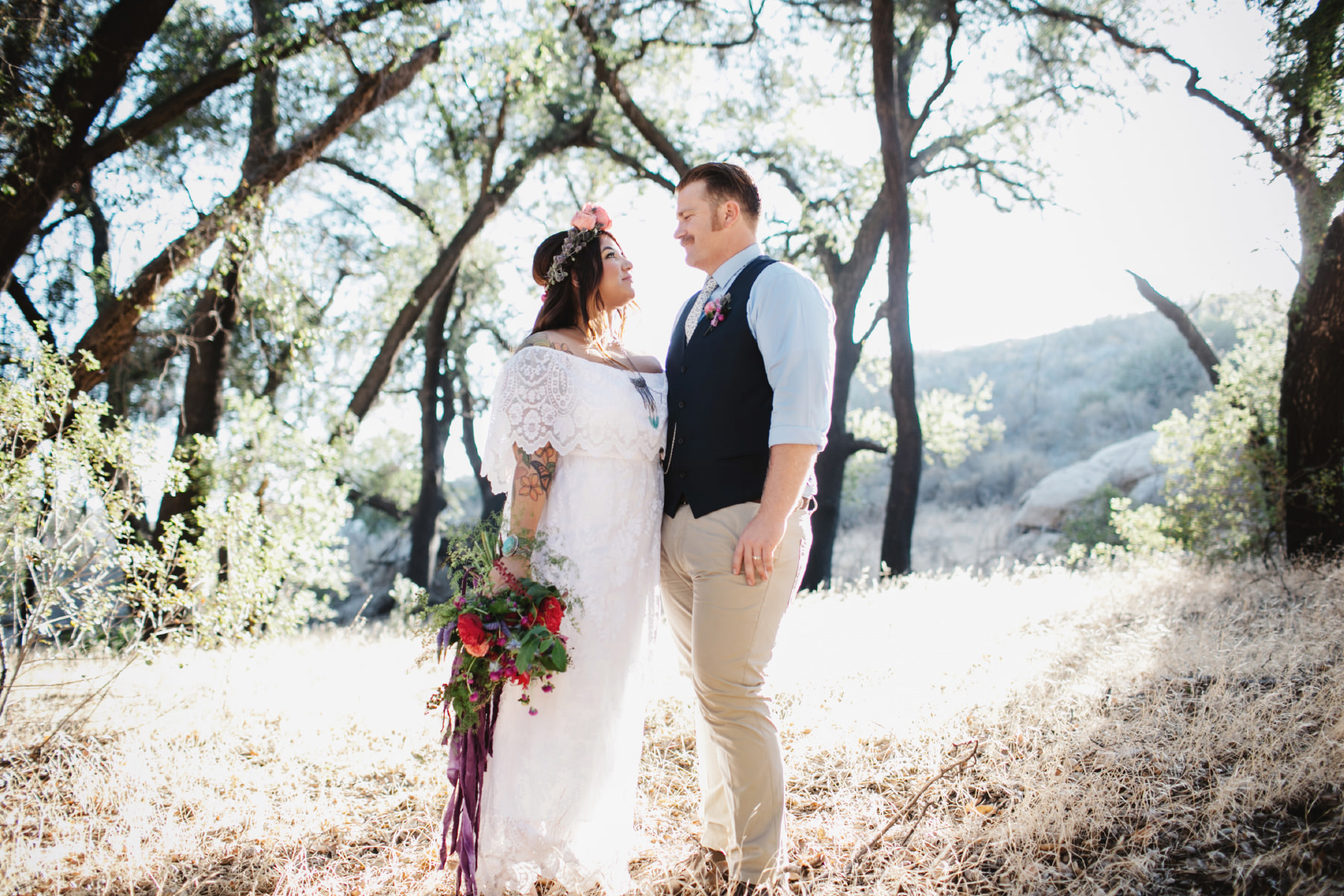 Bride and groom posing in the oak grove at Hidden Oaks Ranch