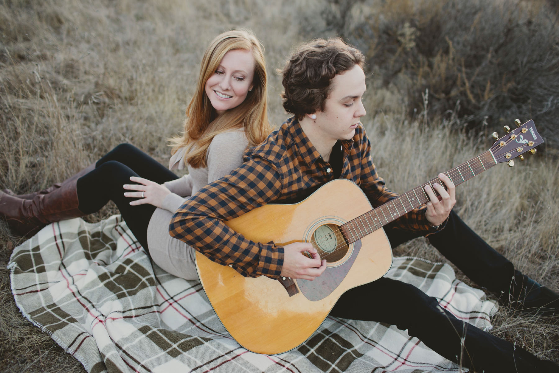 Couple playing guitar on a blanket in a field at Mission Trails
