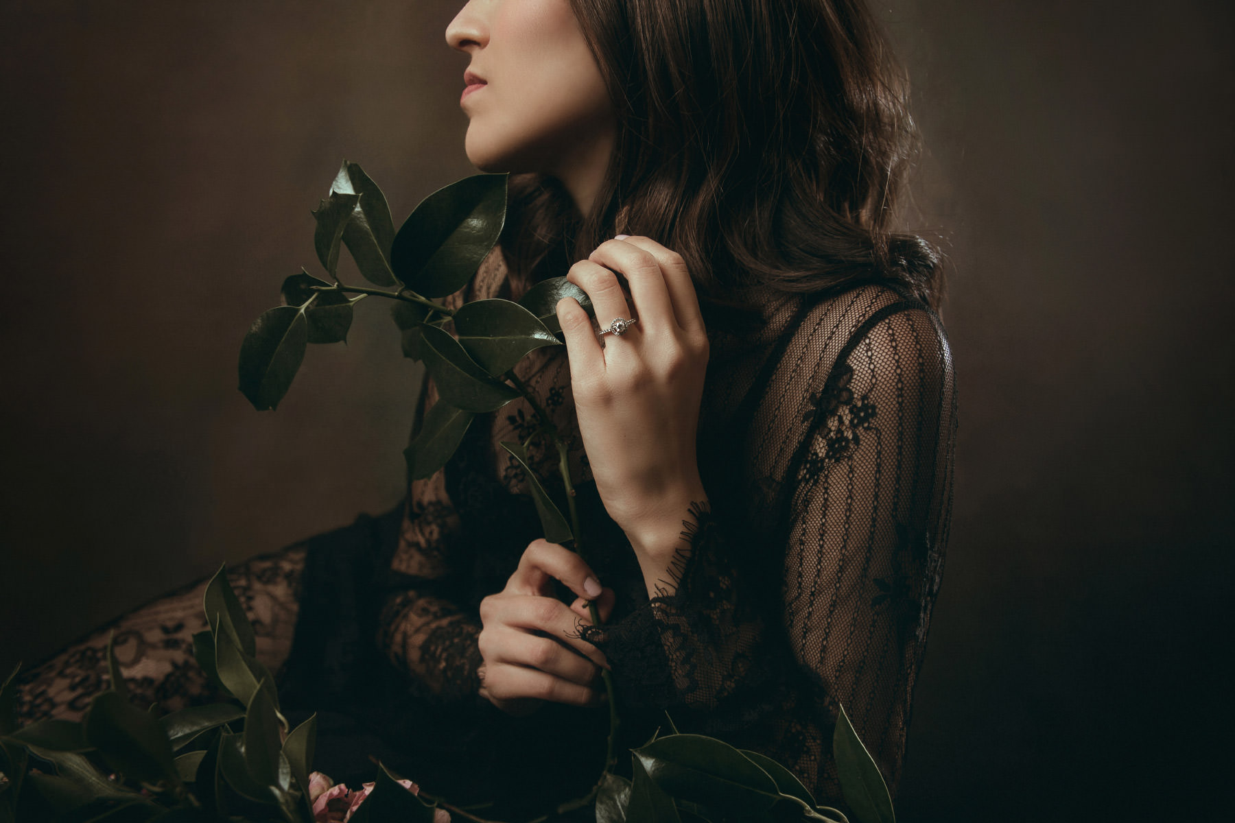 Dark and moody editorial of bride posing with flowers
