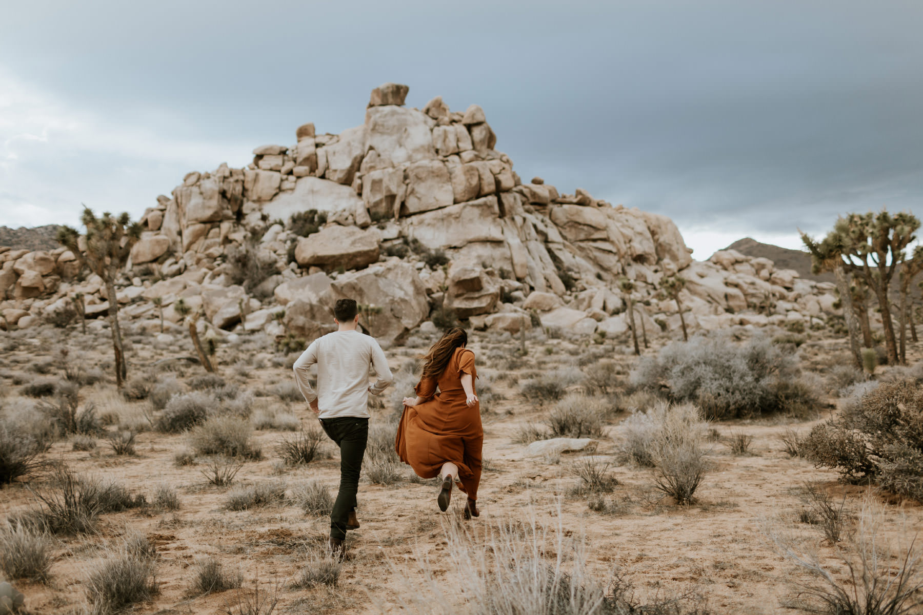 Engaged couple running in Joshua Tree