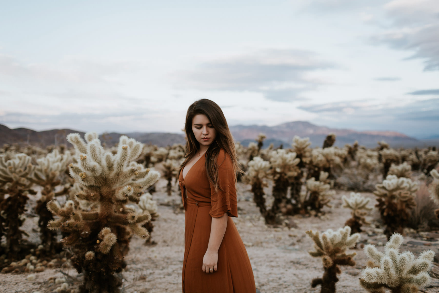 Girl wearing orange maxi dress at Chollas cactus garden in Joshua Tree