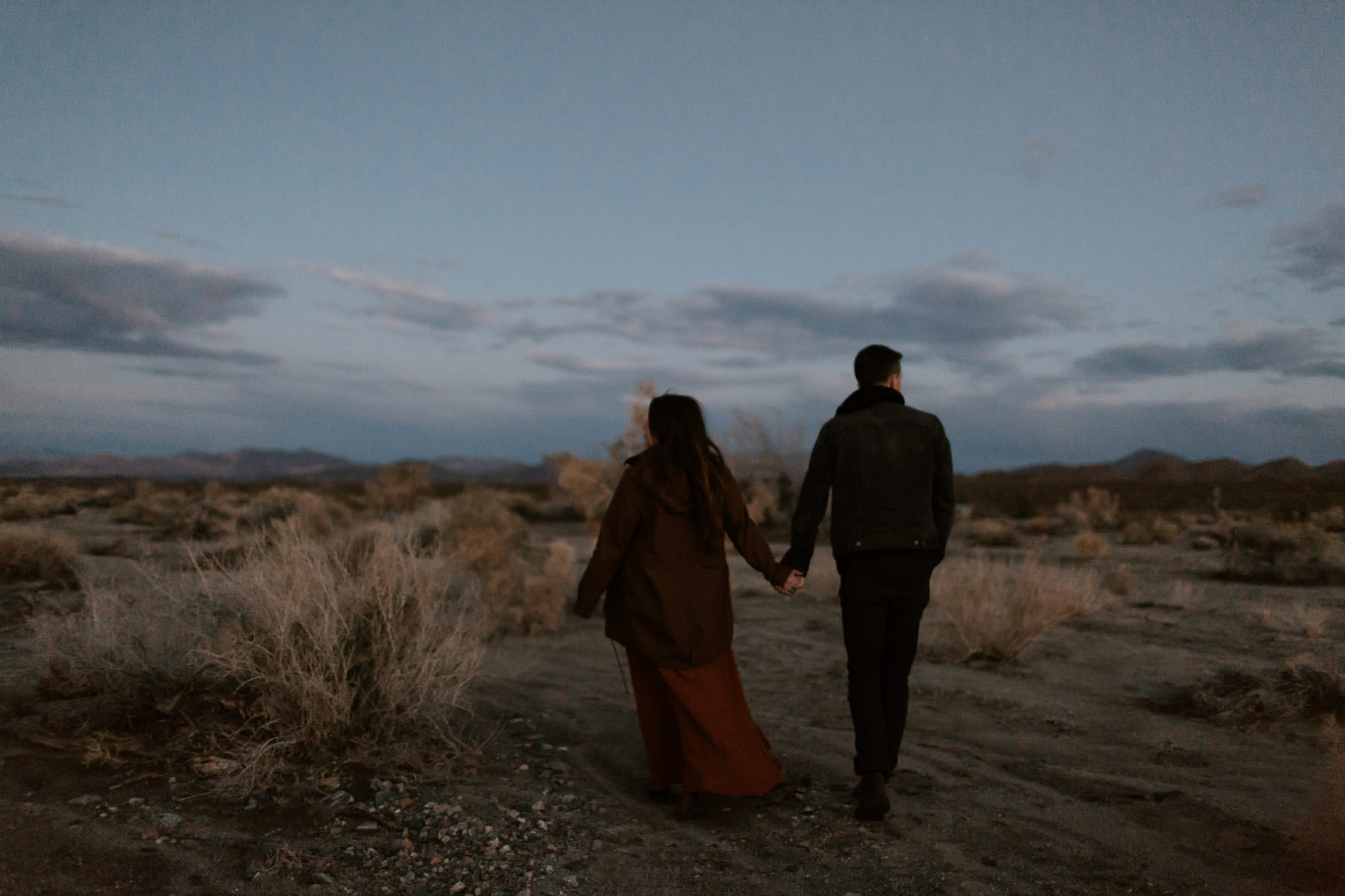 Engaged couple kissing during twilight blue hour in Joshua Tree