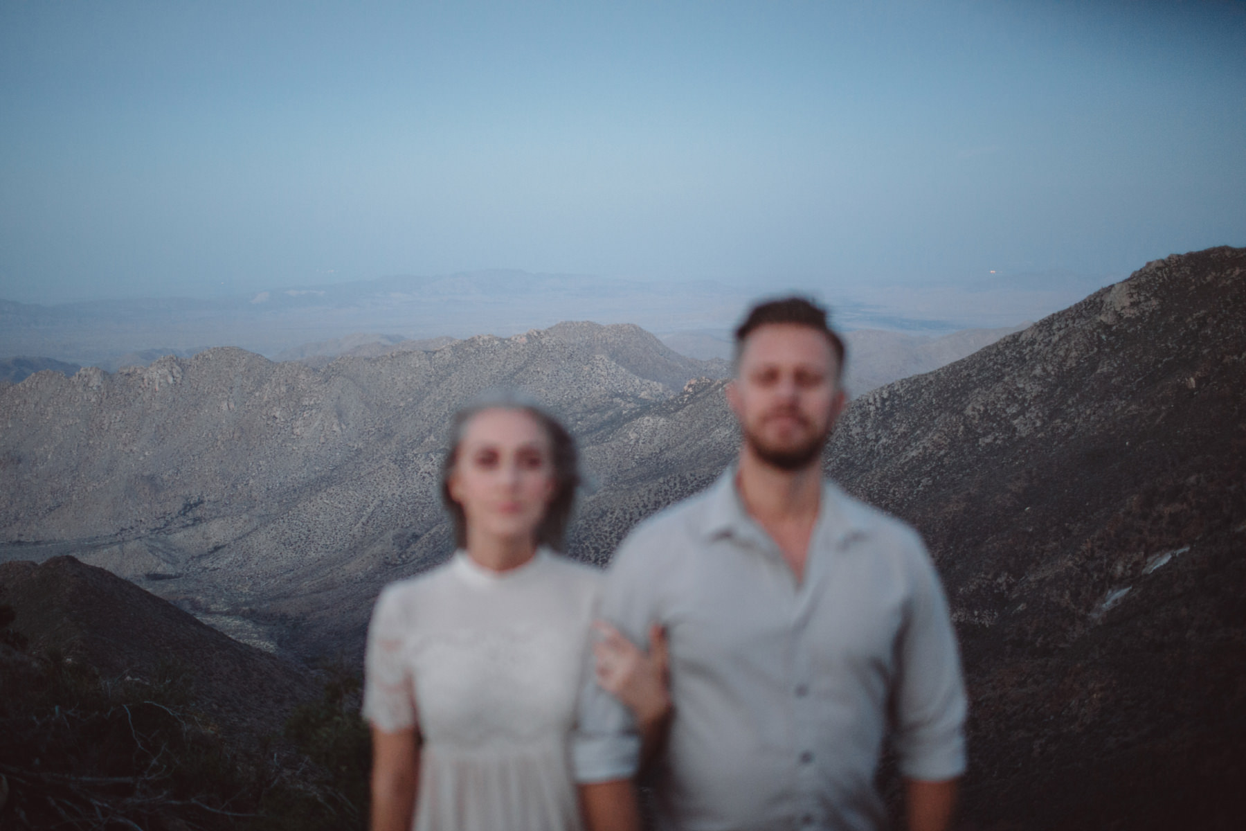 Out of focus couple standing with their eyes closed atop Mount Laguna desert overlook