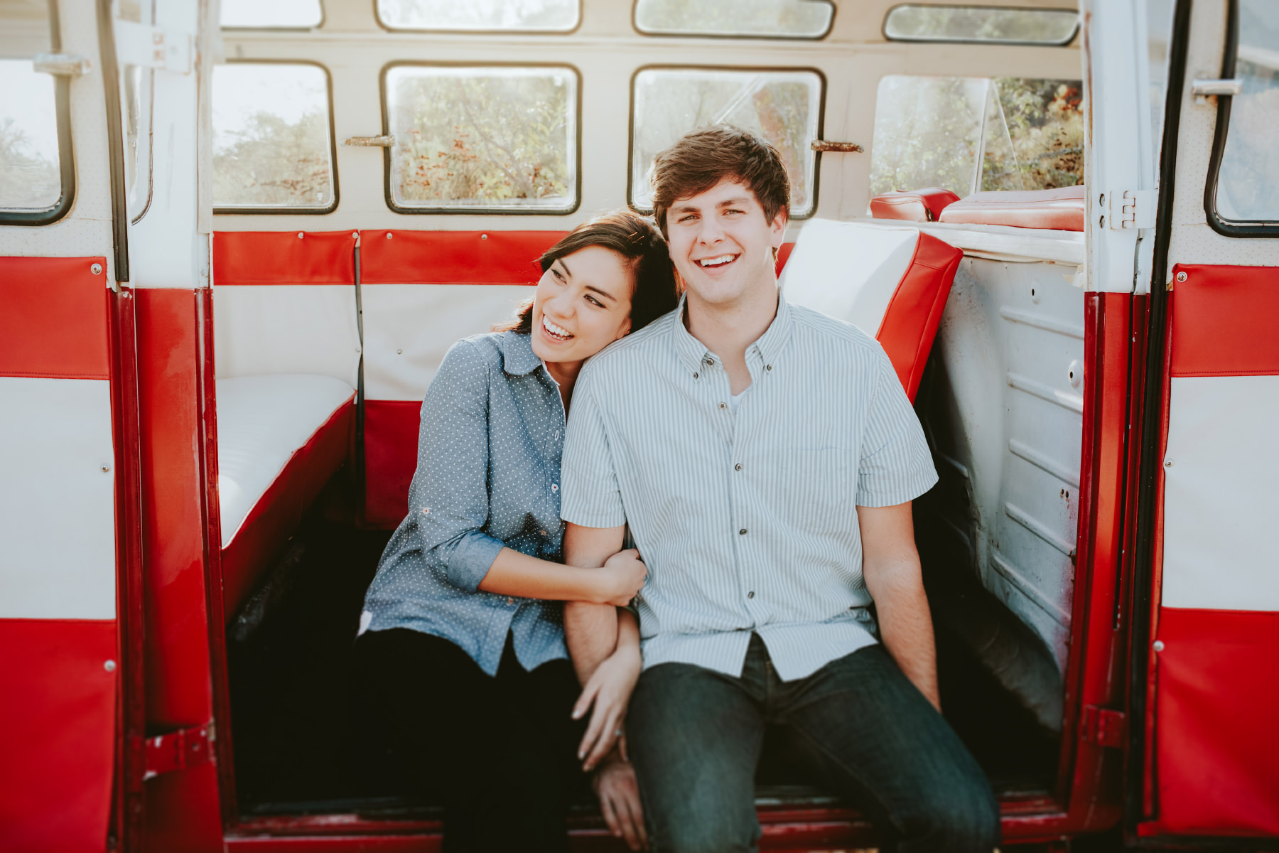 Hip engaged couple laughing in red VW bus