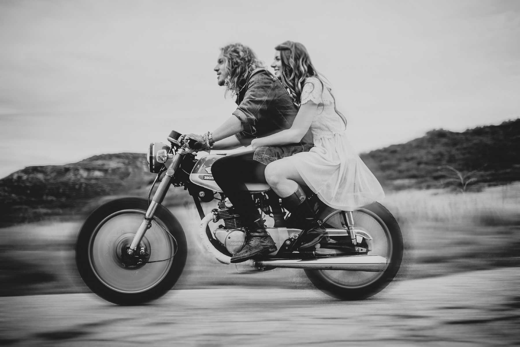 Edgy couple riding a motorcycle together in San Diego