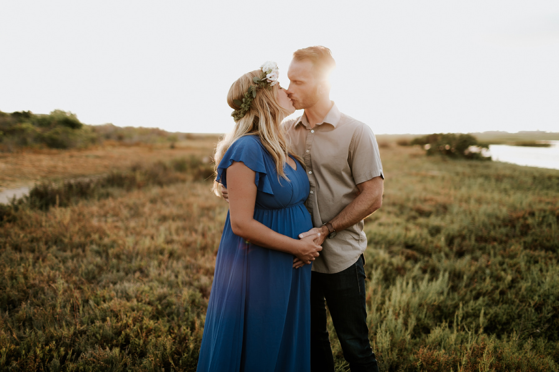 Maternity couple kissing during golden hour at San Elijo Lagoon in San Diego